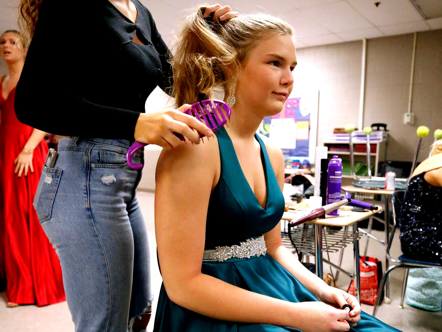 Abby Blythe fixes Taylor Patterson's hair as Patterson gets ready to participate in the Siegel Prom Fashion show on Thursday, Feb. 14, 2019.