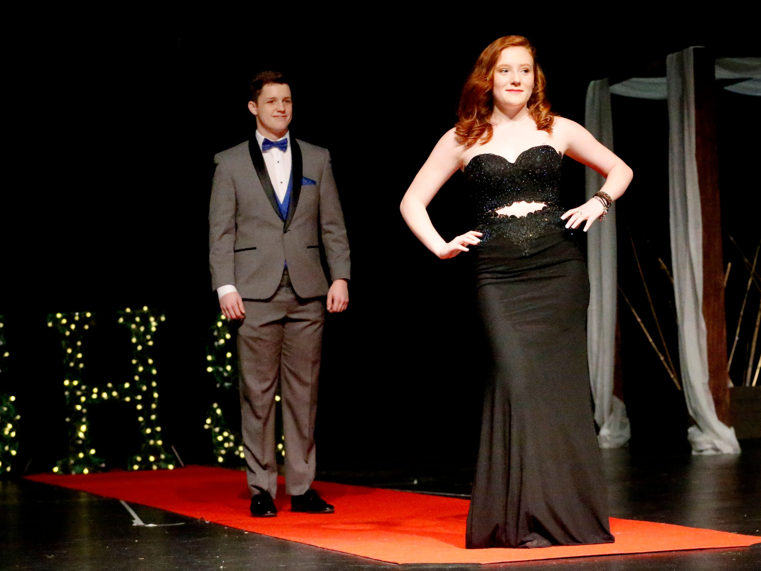 Lauren Meyer steps forward to show off her dress as Andrew Bruce waits to show off his tux during the Siegel Prom Fashion show on Thursday, Feb. 14, 2019.