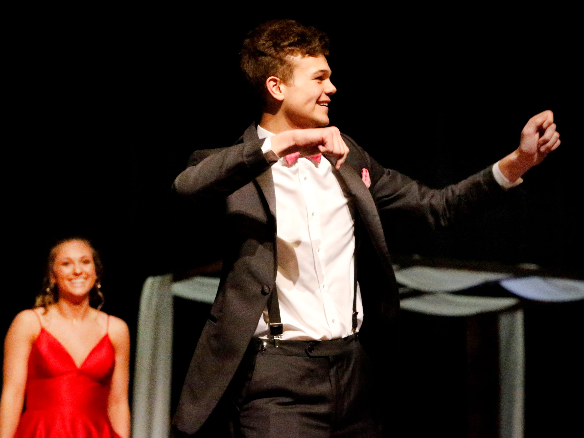 Colin Mathis pretends to pull back a bow at the end of the runway at the Siegel Prom Fashion show on Thursday, Feb. 14, 2019, as he shows off the latest in prom attire.