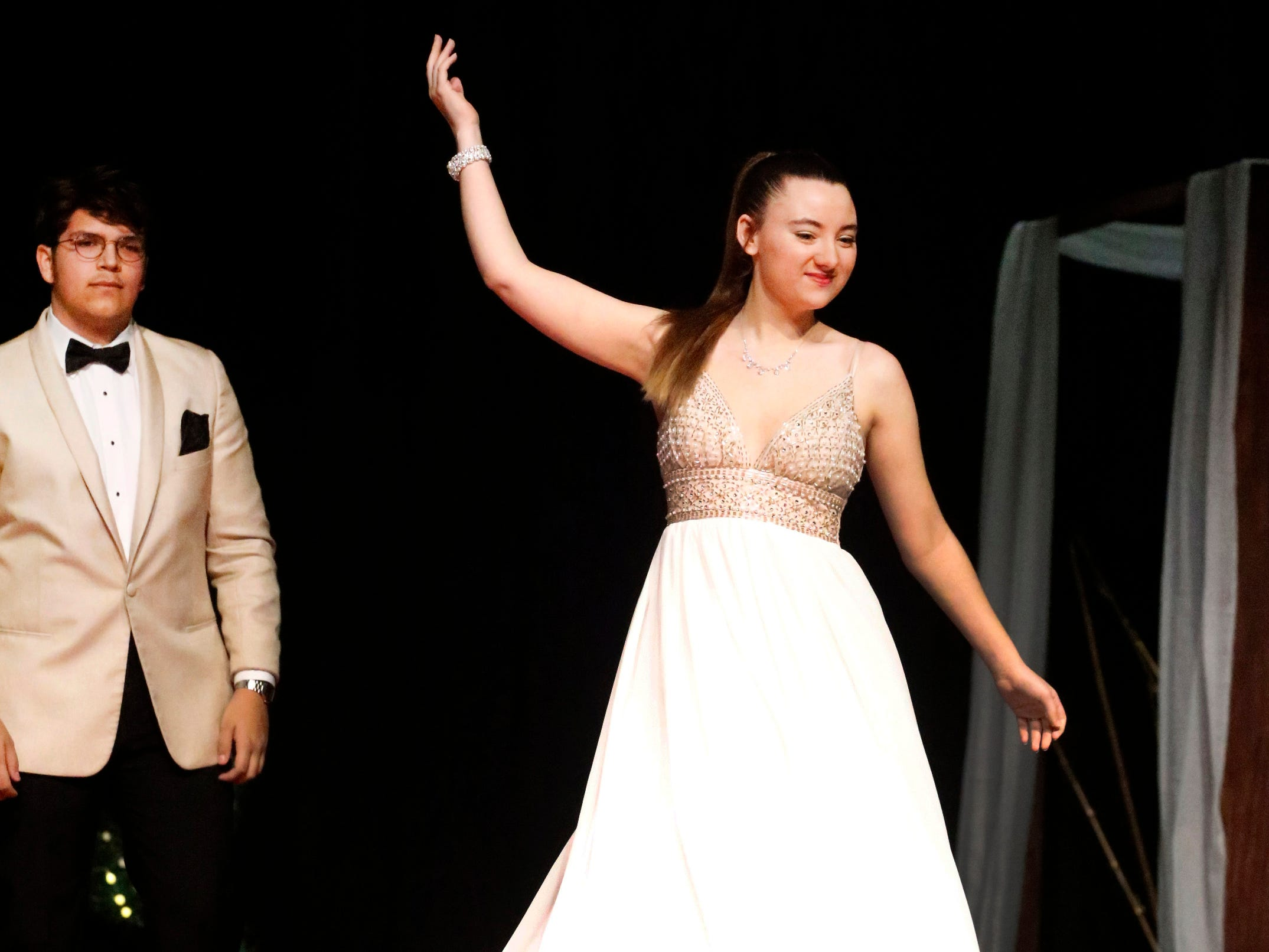 Aubri Shanks steps forward to show off her dress as Marc Padilla waits to show off his tux during the Siegel Prom Fashion show on Thursday, Feb. 14, 2019.