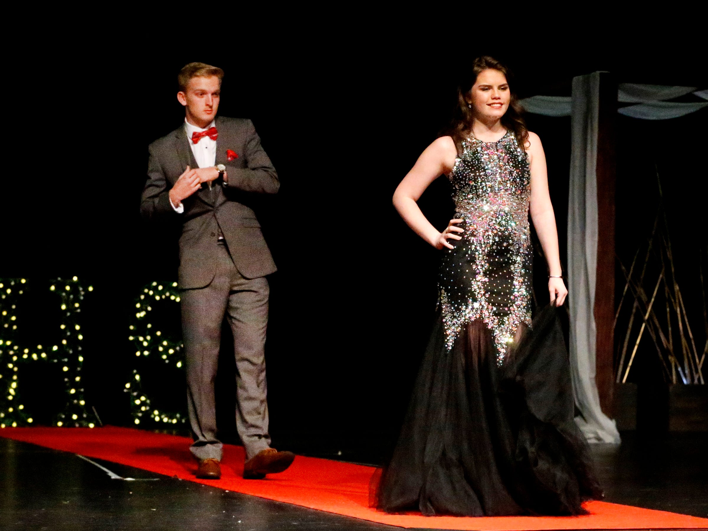 Atlanta Powell steps forward to show off her dress as Jaden Lasley waits to show off his tux during the Siegel Prom Fashion show on Thursday, Feb. 14, 2019.