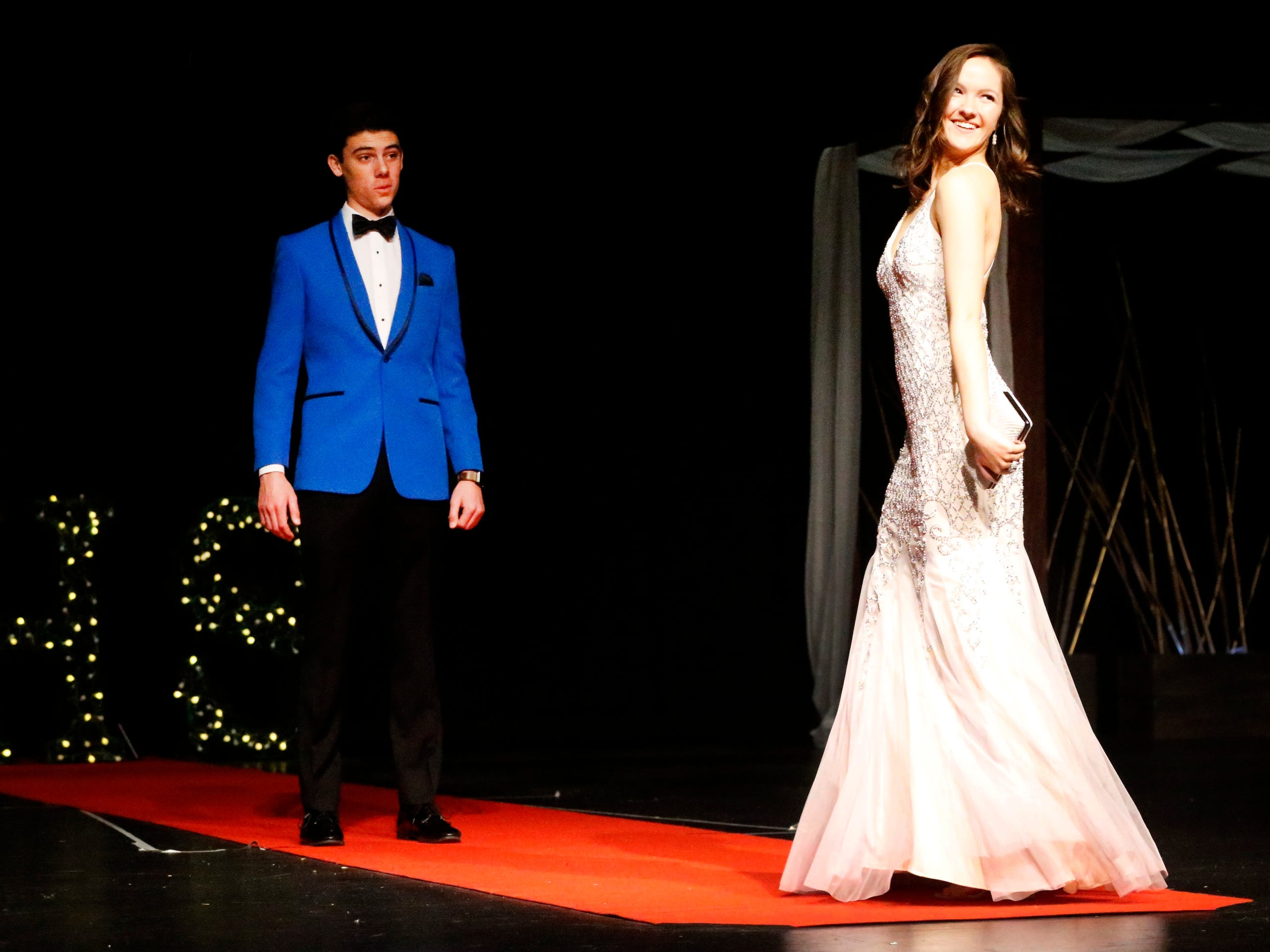 Lucy Bridges steps forward to show off her dress as Adam Lalance waits to show off his tux during the Siegel Prom Fashion show on Thursday, Feb. 14, 2019.