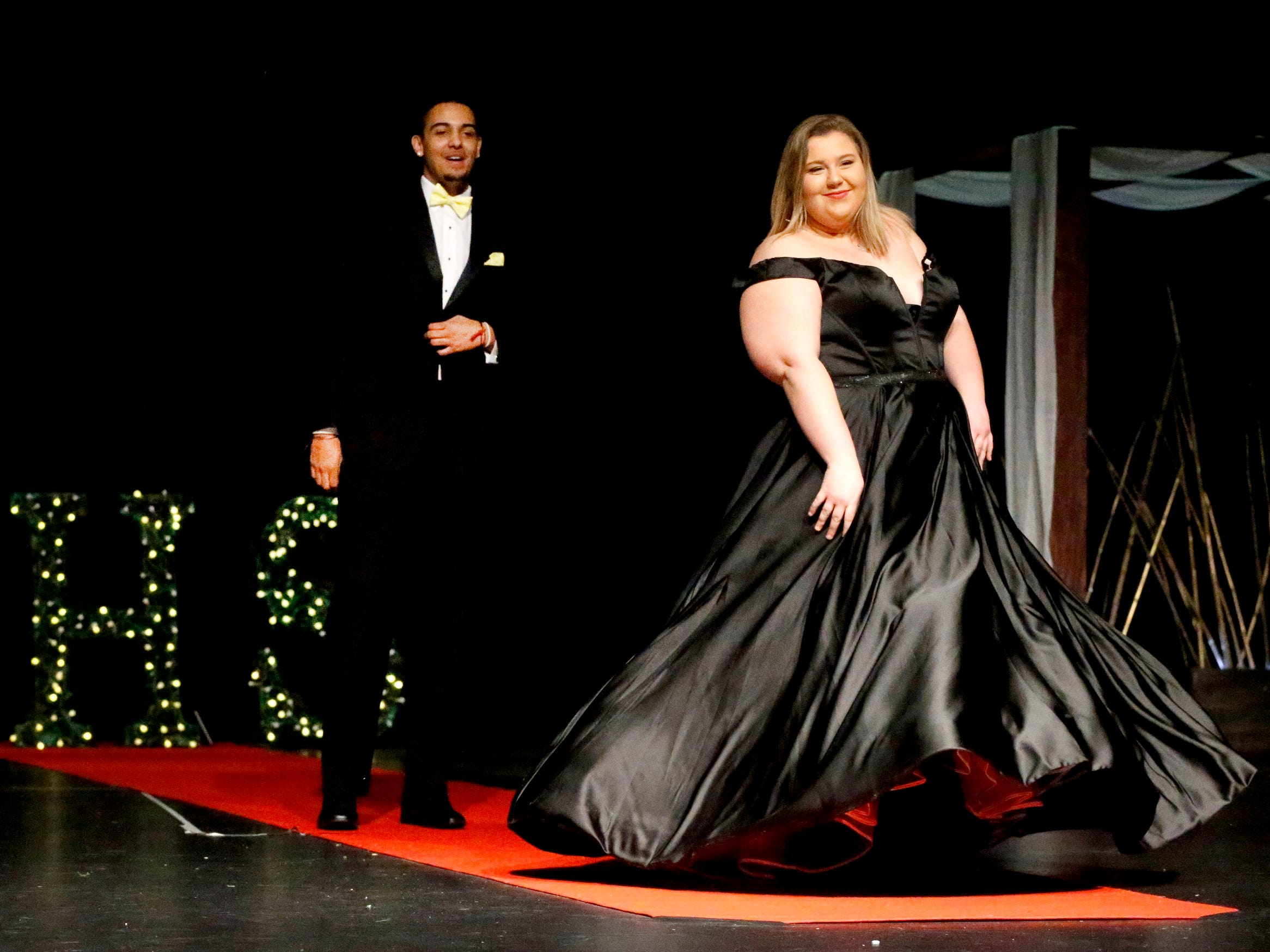 Anna Remkus spins around to show off her dress as O'Brien Gentry waits to show off his tux during the Siegel Prom Fashion show on Thursday, Feb. 14, 2019.