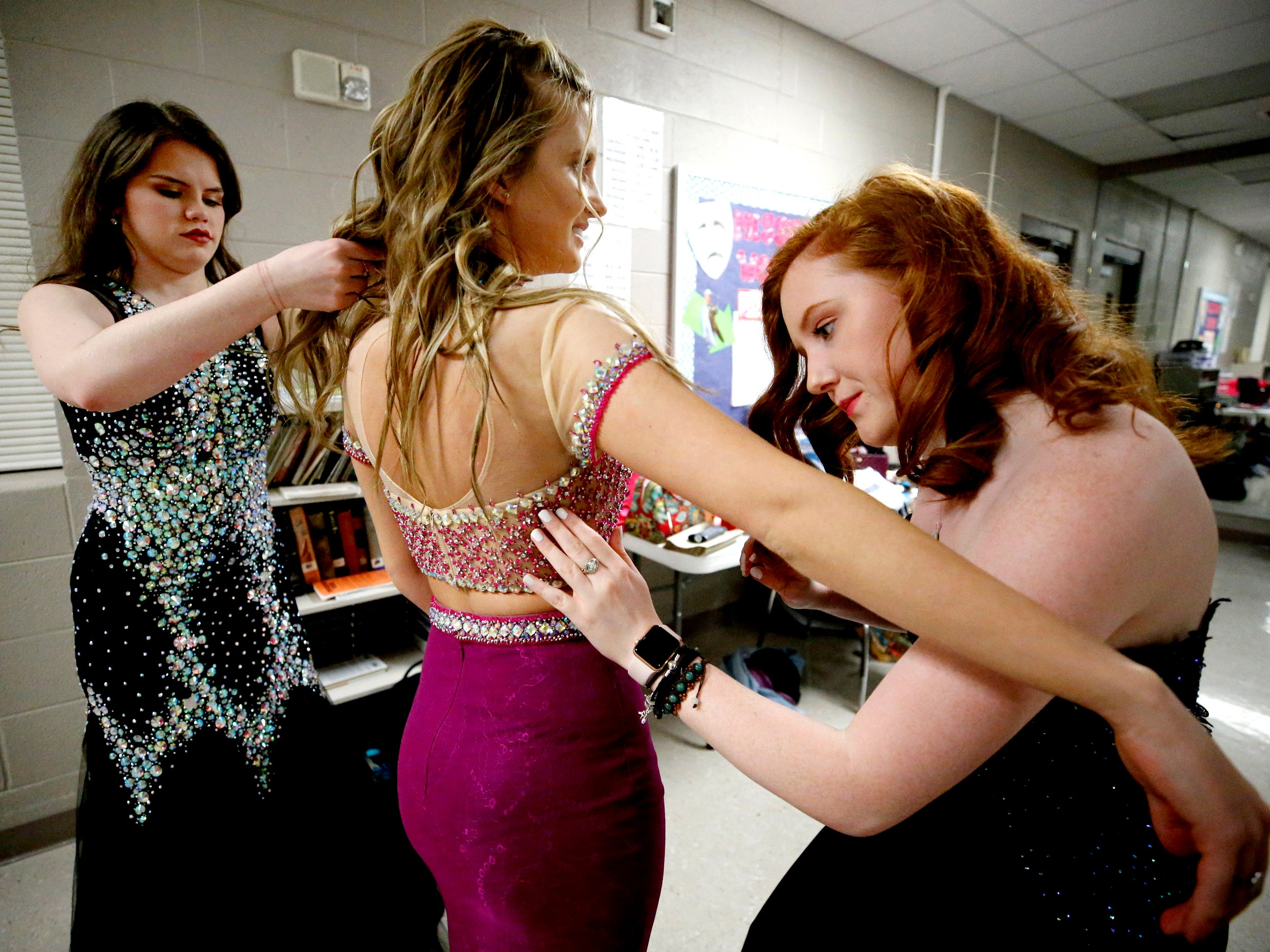 Atlanta Powell, left, and Lauren Meyer, right, help Sara Jarrell get ready for the Siegel Prom Fashion Show on Feb. 14, 2019.