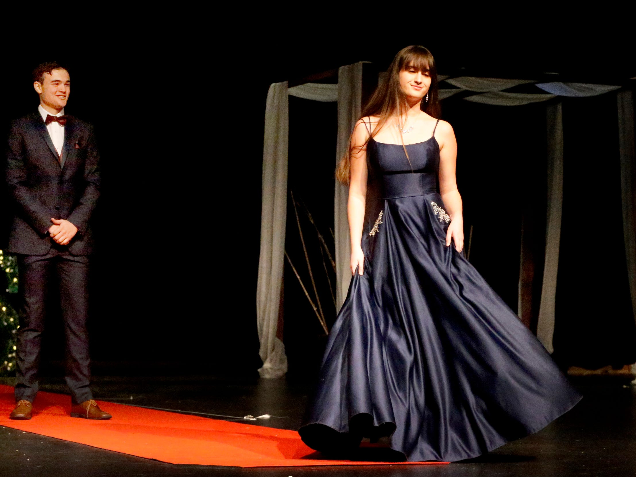 Taya Johnson steps forward to show off her dress as Zane Furqa waits to show off his tux during the Siegel Prom Fashion show on Thursday, Feb. 14, 2019.