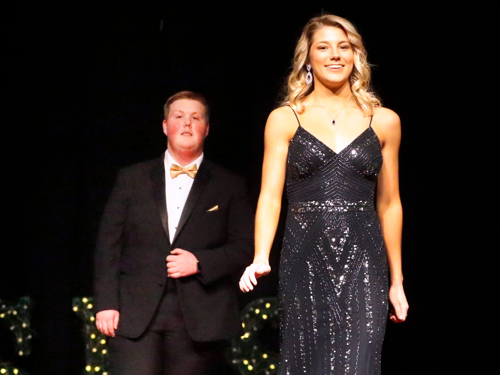 Presley Leebrick steps forward to show off her dress as Hunter Paschall waits to show off his tux during the Siegel Prom Fashion show on Thursday, Feb. 14, 2019.