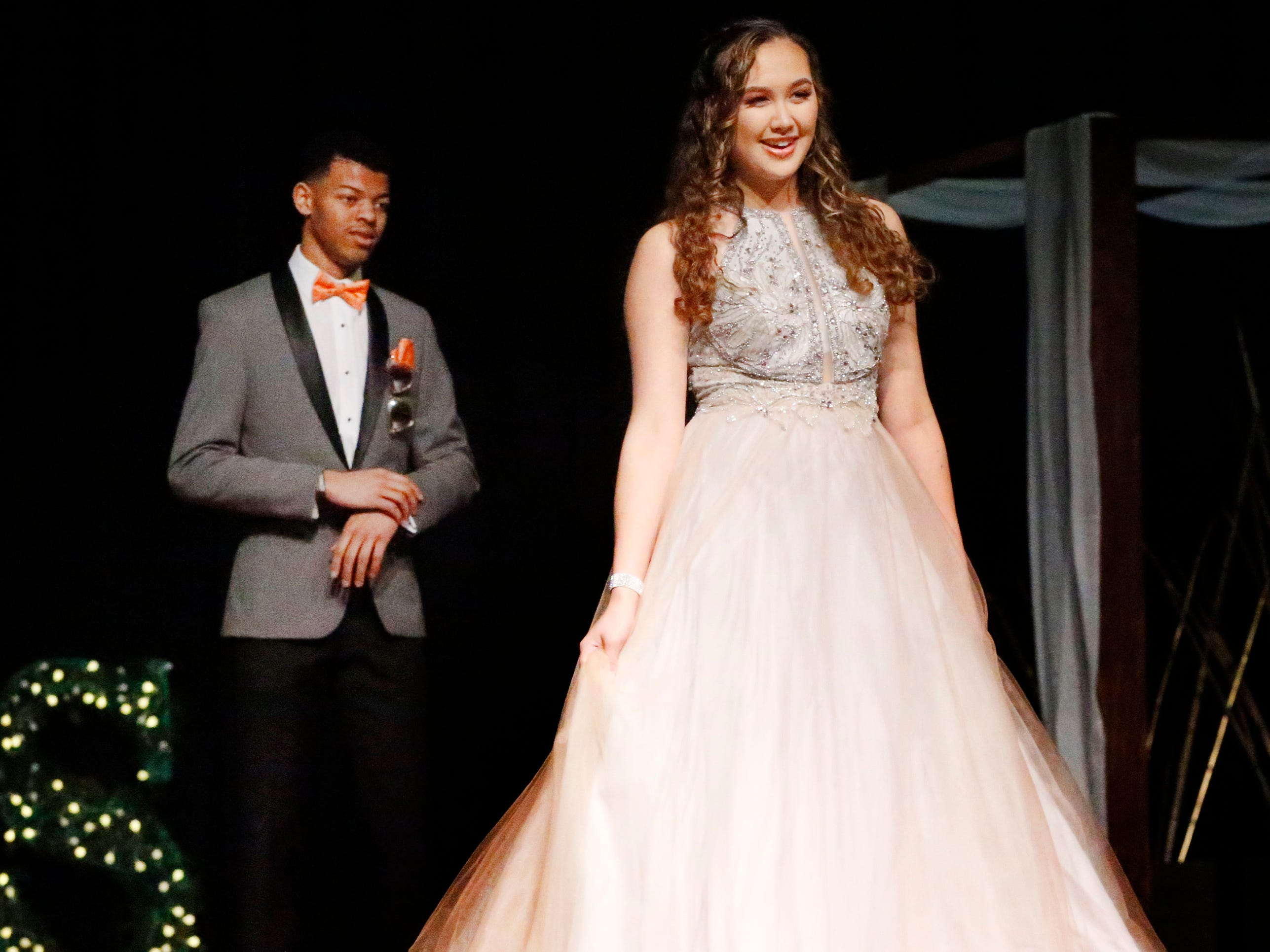 Jasmine Huntsman steps forward to show off her dress as Jaylen Avant waits to show off his tux during the Siegel Prom Fashion show on Thursday, Feb. 14, 2019.