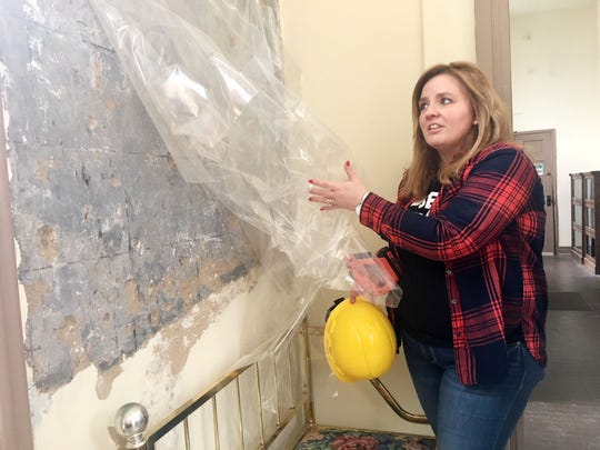 Rachael Finch pulls back the clear sheet on Feb. 14, 2019, to show the signatures of men wrote on the wall during the Civil War.