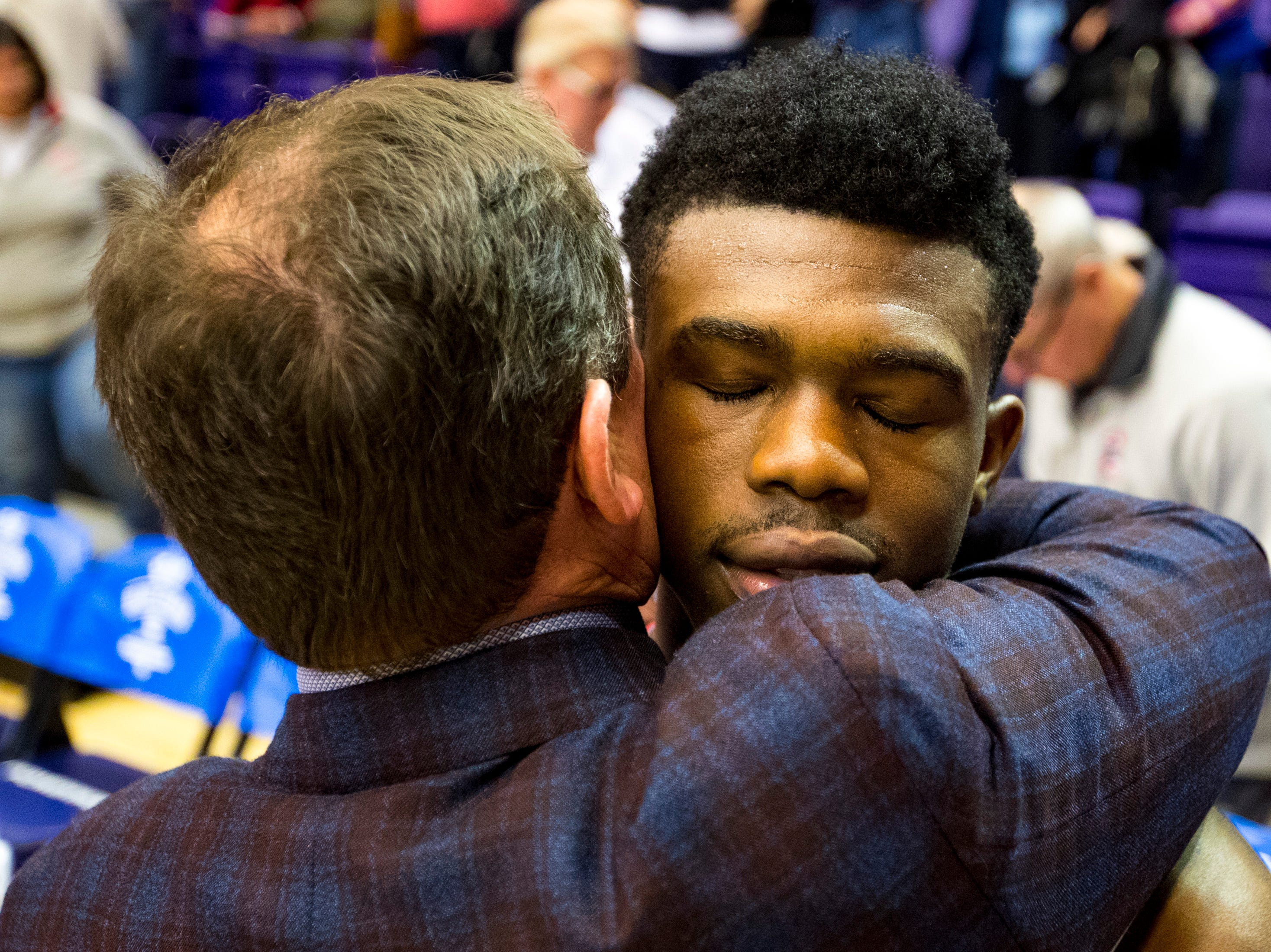 Brentwood Academy's Marcus Fitzgerald (5) gets a hug from Brentwood Academy's head coach Hubie Smith after Brentwood Academy's game against Baylor in the semifinal round of the TSSAA Division II Class AA State Championships at Lipscomb University's Allen Arena in Nashville on Thursday, Feb. 28, 2019.