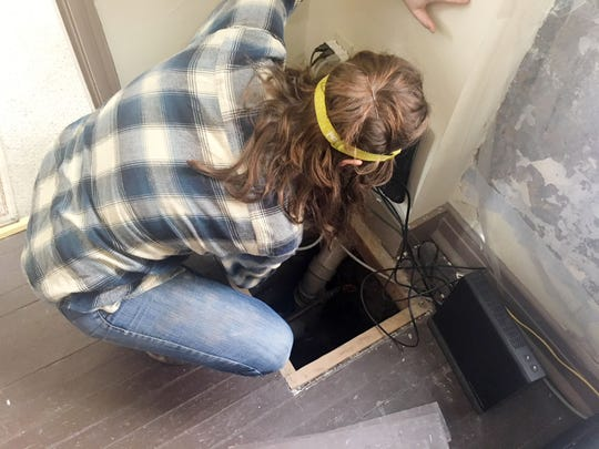 Grace Abernethy opens up another small crawlspace area underneath the front of the building on Feb. 14, 2019.