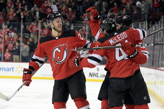 New Jersey Devils center Kevin Rooney celebrates his short-handed goal with Michael McLeod (41) and Mirco Mueller, left, during the second period of an NHL hockey game against the Calgary Flames Wednesday, Feb. 27, 2019, in Newark.