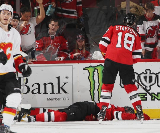 NEWARK, NEW JERSEY - FEBRUARY 27: Mirco Mueller #25 of the New Jersey Devils is injured during the third period injury against the Calgary Flames  at the Prudential Center on February 27, 2019 in Newark, New Jersey. The Flames defeated the devils 2-1.