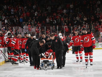 NEWARK, NEW JERSEY - FEBRUARY 27: Mirco Mueller #25 of the New Jersey Devils is taken off the ice after a third period injury against the Calgary Flames  at the Prudential Center on February 27, 2019 in Newark, New Jersey. The Flames defeated the devils 2-1.