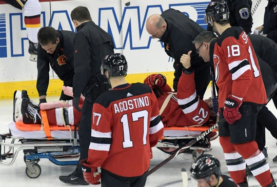 New Jersey Devils defenseman Mirco Mueller gives a thumbs-up sign as he is wheeled off the ice on a stretcher after being injured during the third period of an NHL hockey game against the Calgary Flames Wednesday, Feb. 27, 2019, in Newark, N.J. The Flames defeated the Devils 2-1.