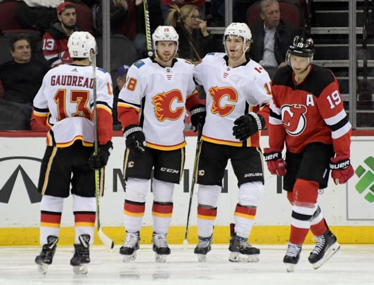 Calgary Flames center Elias Lindholm (28) celebrates his goal with Johnny Gaudreau (13) and Matthew Tkachuk as New Jersey Devils center Travis Zajac, right, reacts during the second period of an NHL hockey game Wednesday, Feb. 27, 2019, in Newark, N.J.