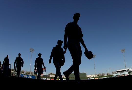 Players for the against the Chicago Cubs walk off the field after their baseball game against the Texas Rangers Wednesday, Feb. 27, 2019, in Surprise, Ariz.