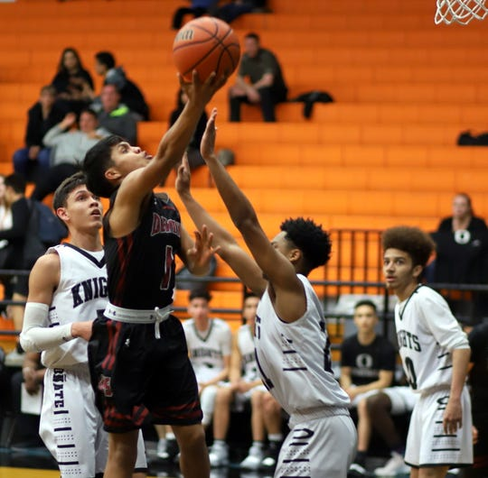 Sophomore Wildcat Jordan Caballero attacked the basket defended by a trio of Knights during Wednesday's 63-52 District 3-5A loss to the host Onate high Knights.