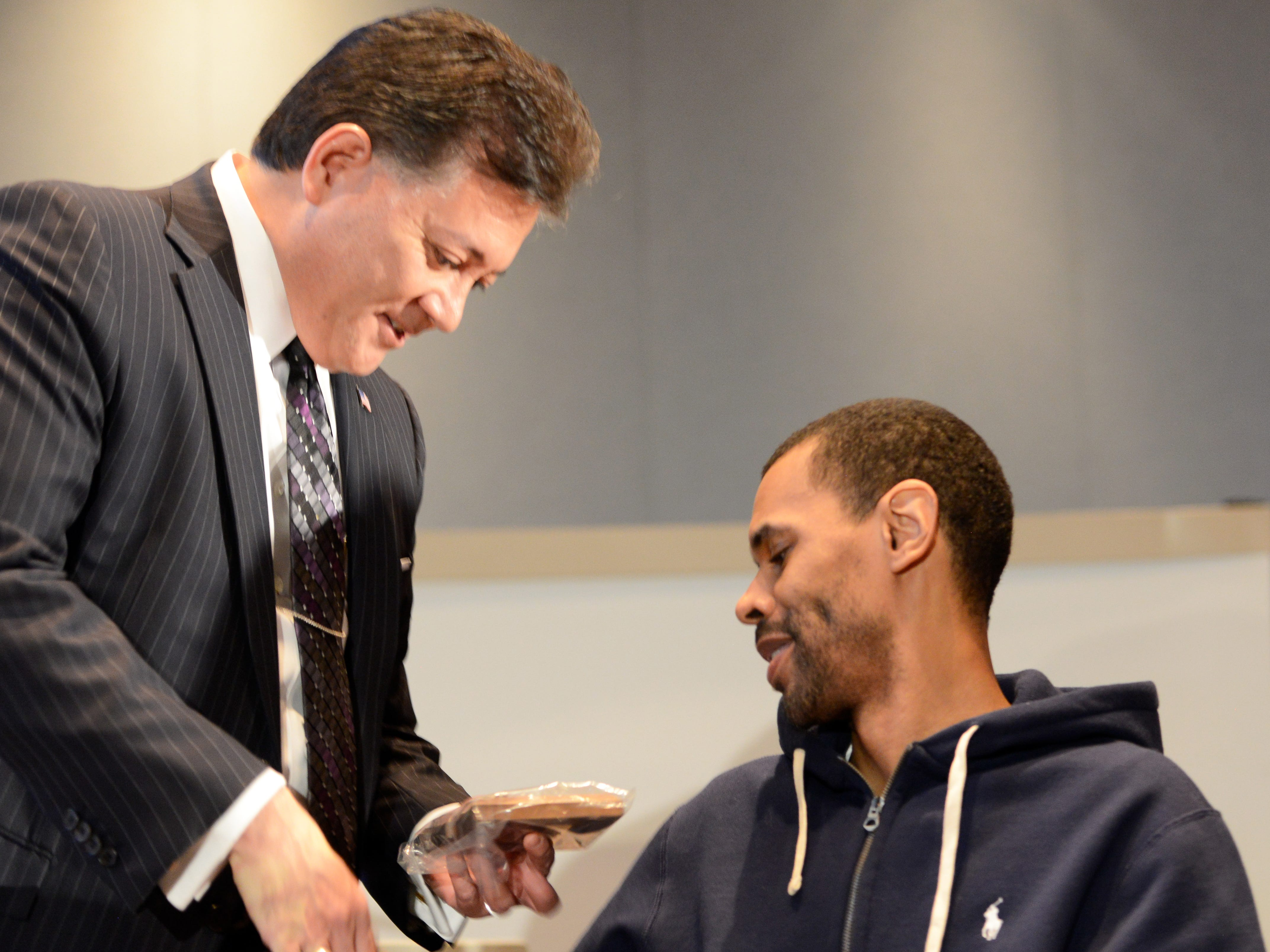"""Mayor Ken Miyagishima presents a key to the city to former New Mexico State University basketball player Shawn Harrington, who was paralyzed in a gun attack in his hometown of Chicago, after the mayor's """"State of the City"""" address on Thursday, Feb. 28, 2019."""