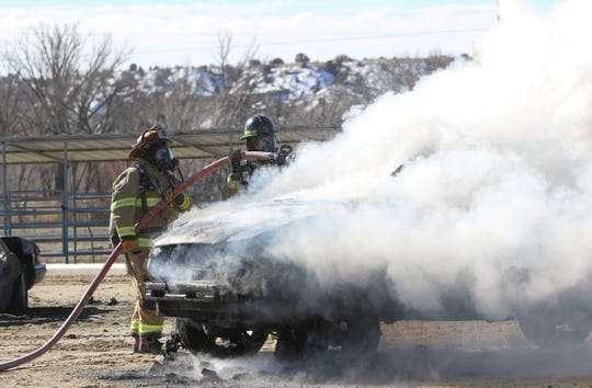 From left, Caitlyn Vecellio and Hunter Randolph, volunteer firefighters with the San Juan County Fire Department, douse a mock van fire on Wednesday at McGee Park in Farmington.