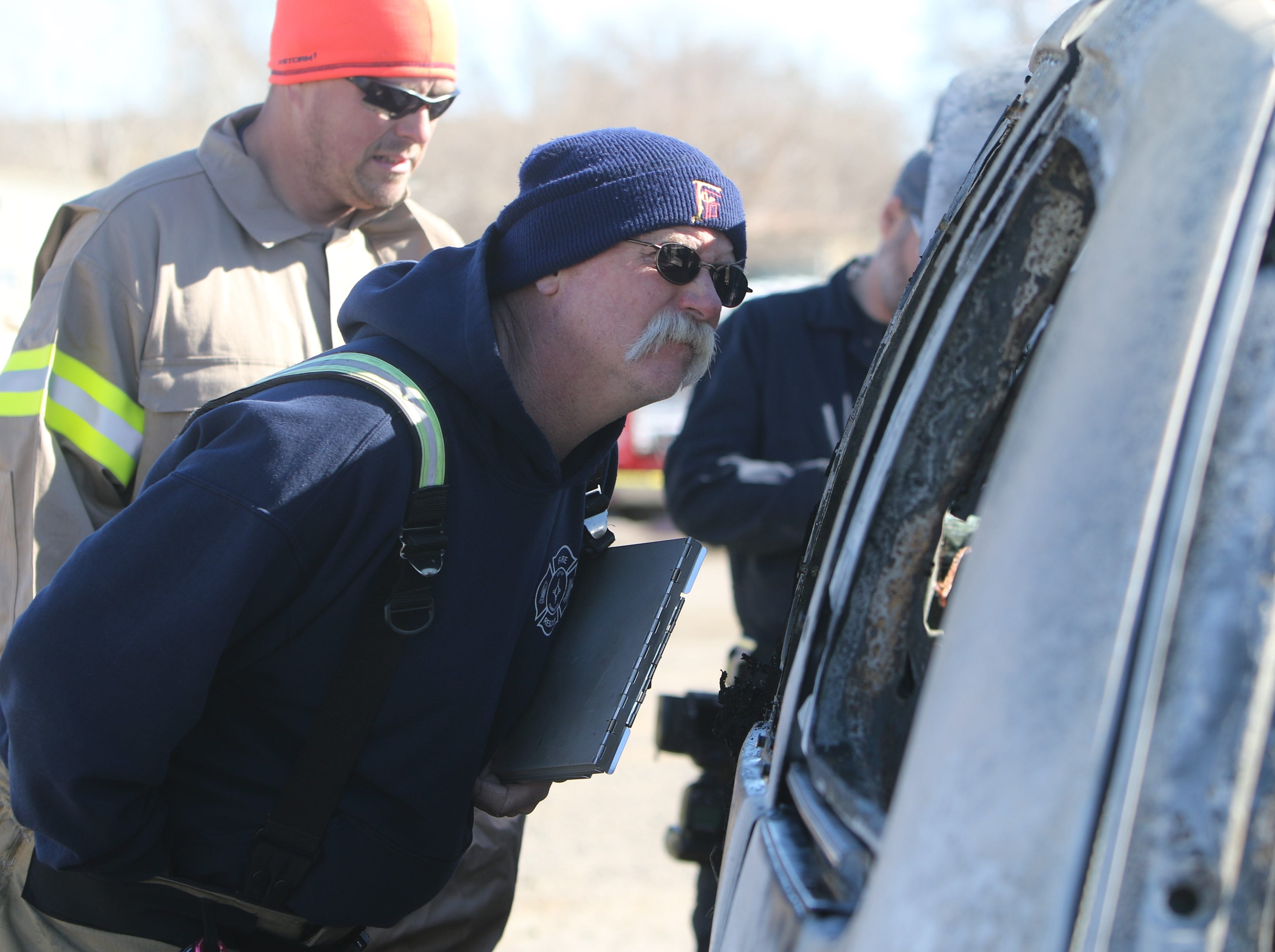 Kipp Rix, a fire investigator with the Farmington and San Juan County fire departments, examines the remains of a charred van as part of a training exercise on Wednesday.