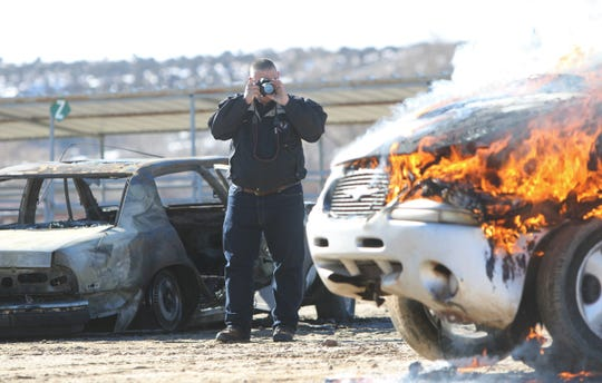 Stephen Rinaldi, senior fire and life safety coordinator for the Los Alamos Fire Department, takes a photo of the mock auto fire during fire investigation training at McGee Park on Wednesday.