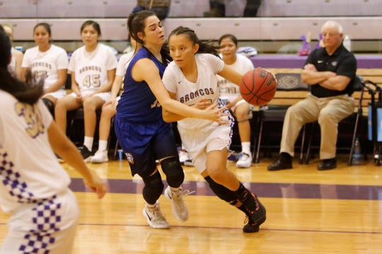 Kirtland Central's Avery Begay drives toward the basket against Bloomfield's Lanay Gutierrez during Wednesday's District 1-4A tournament semifinals at Bronco Arena in Kirtland.