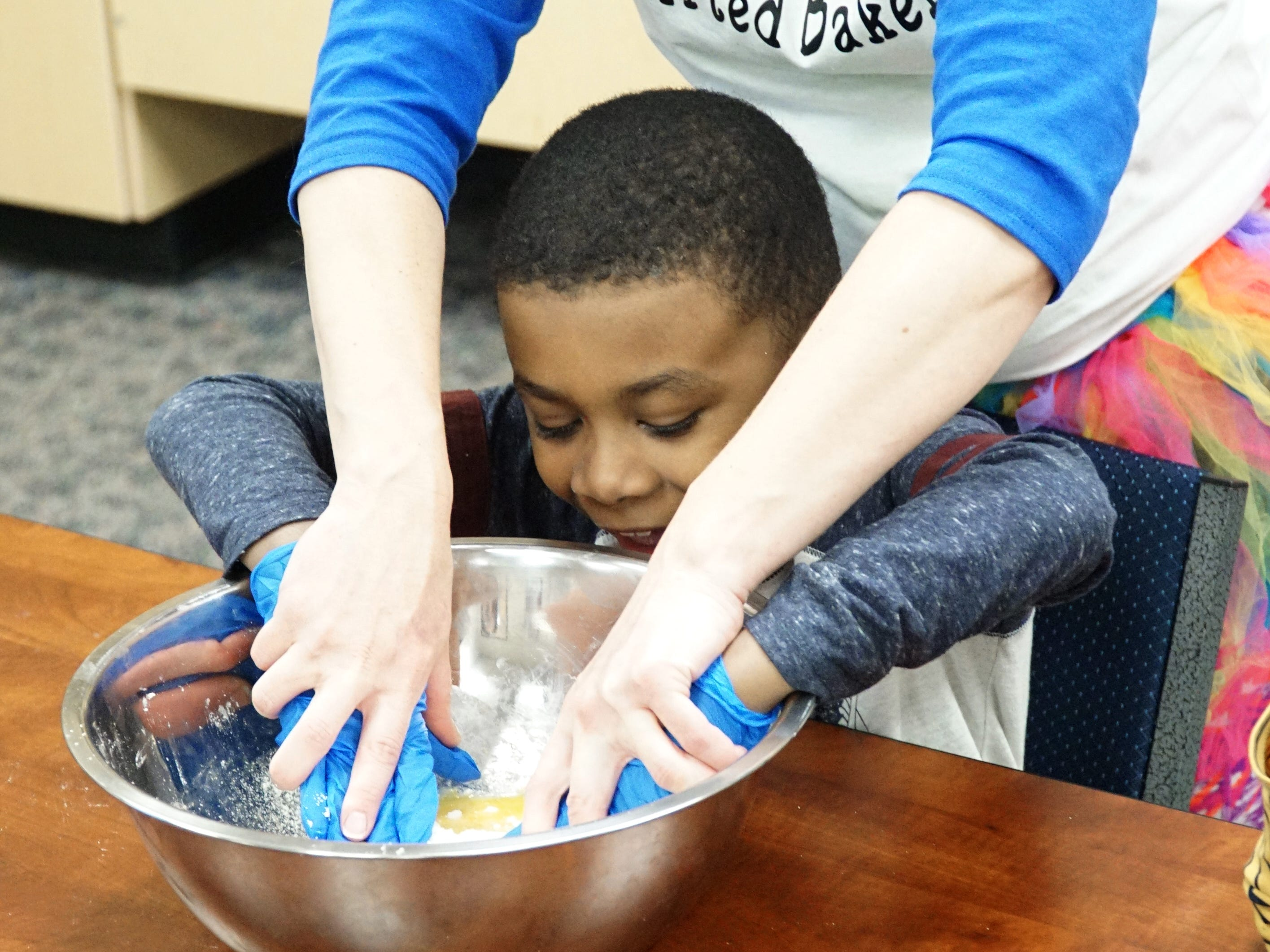 Teacher Briona McKinney helps Payce Jenkins mix the cookie dough with his hands.