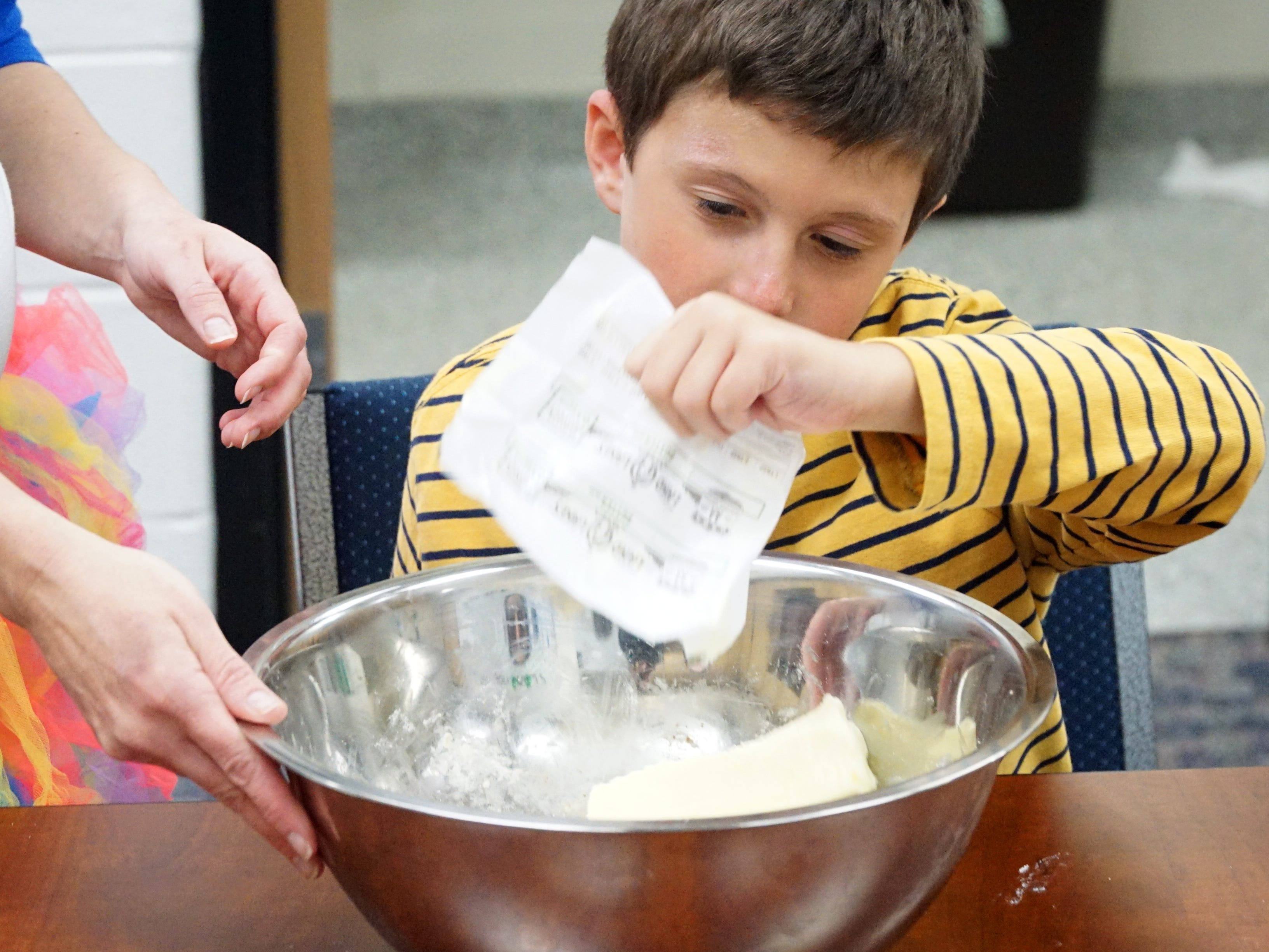 Harlan Elementary School student Christian Vuljaj drops a stick of butter into some cookie mix on Feb. 28 as the school's group of special needs students work on baking some treats to help raise funds so that they can purchase a service dog.