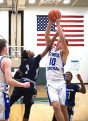 Catholic Central player Mike Harding, right, rips a rebound down in front of Farmington's Jailin Lee on Feb. 27.