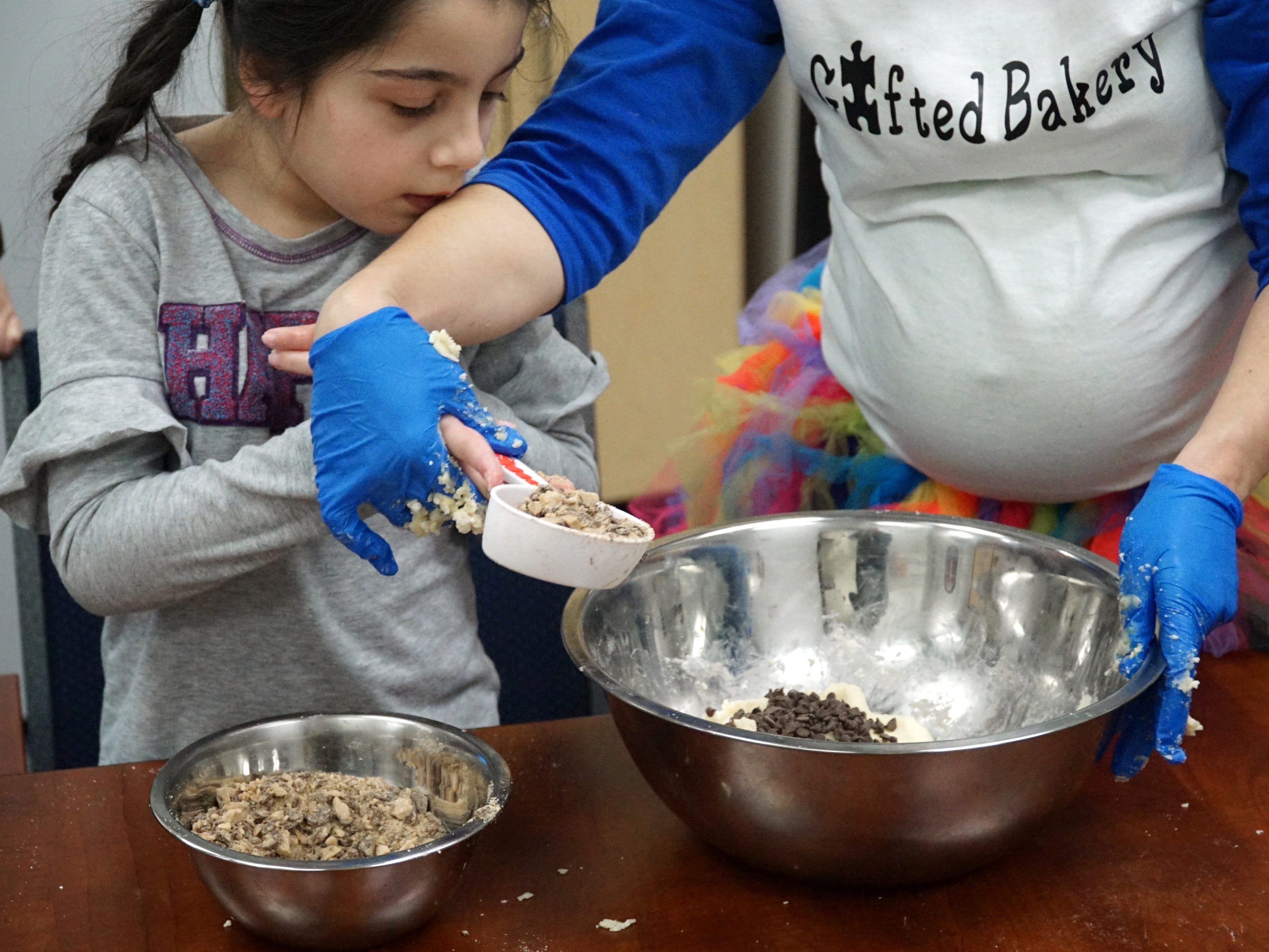 Grace Karim helps to add the toffee chips to the cookie dough at Harlan Elementary.