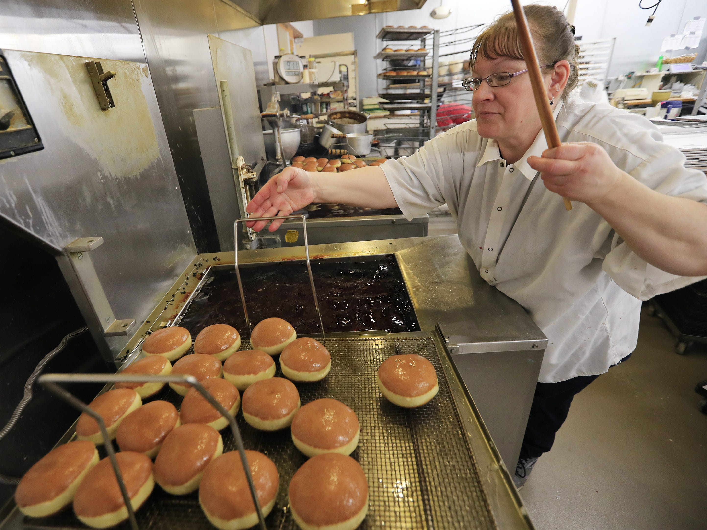 Janice Smurawa takes a batch of paczki out of the fryer at Smurawa's Country Bakery on Tuesday, Feb. 26, 2019, in Pulaski.