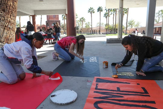 From left, Charity Stagg, Ally Grein and Samira Diaz paint signs to welcome the students from Parkland who will be at Palm Springs High School to speak about gun violence, February 28, 2019.