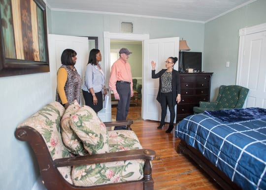 From left, Renee Watson, Greater Little Rock Baptist Church singles ministry facilitator; Impact 100 President Brigette Brooks; and Dick Baker, board member for Re-Entry Alliance Pensacola, listen Thursday as Nicole Cleckler, REAP women's director and case manager, gives a tour of the new REAP transitional home for women in Pensacola.
