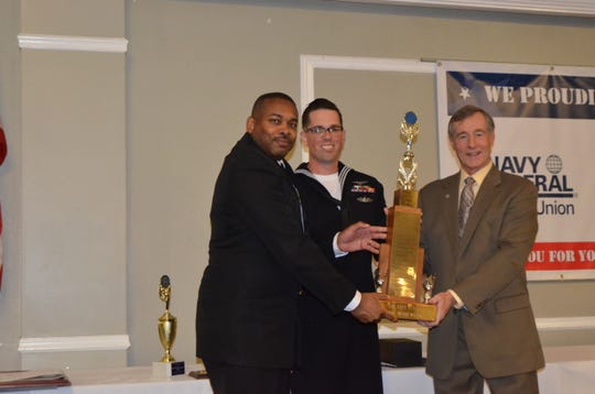 Petty Officer 1st Class Brian Clark, center,receives the Margaret Flowers Civic Award trophy from the Pensacola Council Navy League in a luncheon Feb. 21. Supporting him was NAS Whiting Field Command Master Chief Chris Leonard.