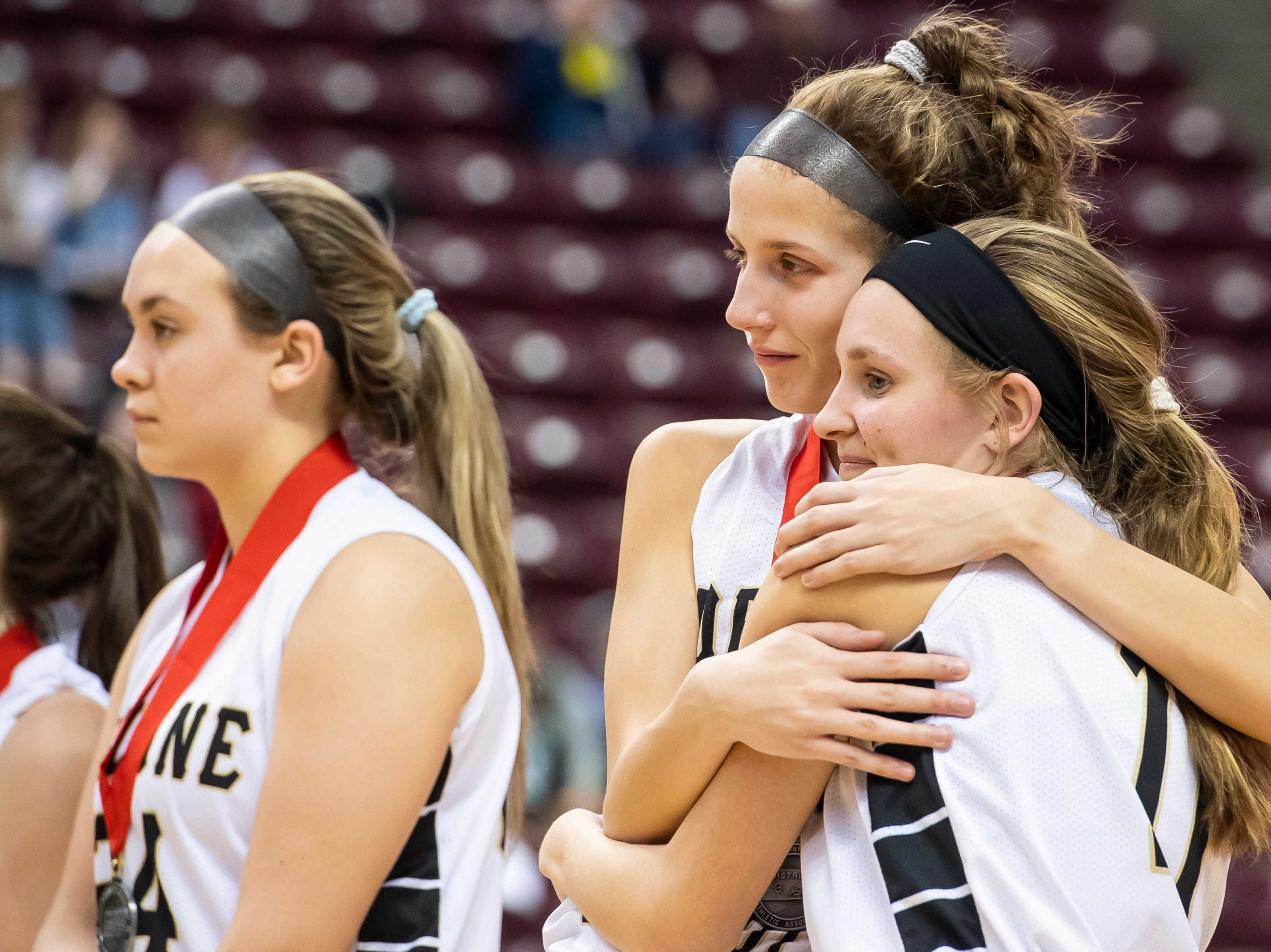 Delone Catholic's Maggie Wells, back, and Riley Vingsen hug after falling to Trinity in the District 3 3A girls championship game against Trinity at the Giant Center in Hershey Wednesday, Feb. 27, 2019. The Squirettes fell 44-33.