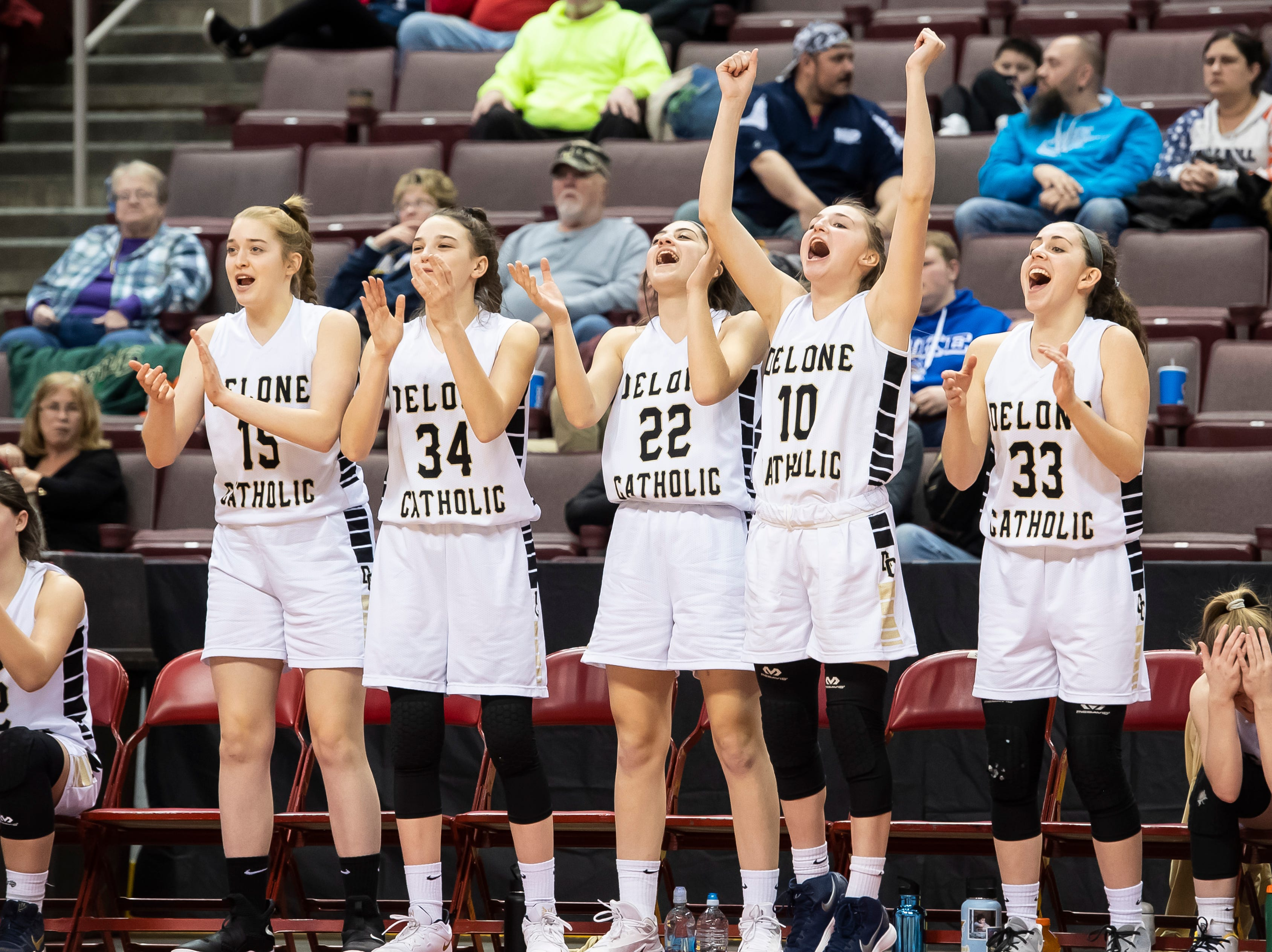 The Delone Catholic bench celebrates after the Squirettes score during the District 3 3A girls championship game against Trinity at the Giant Center in Hershey Wednesday, Feb. 27, 2019. The Squirettes fell 44-33.