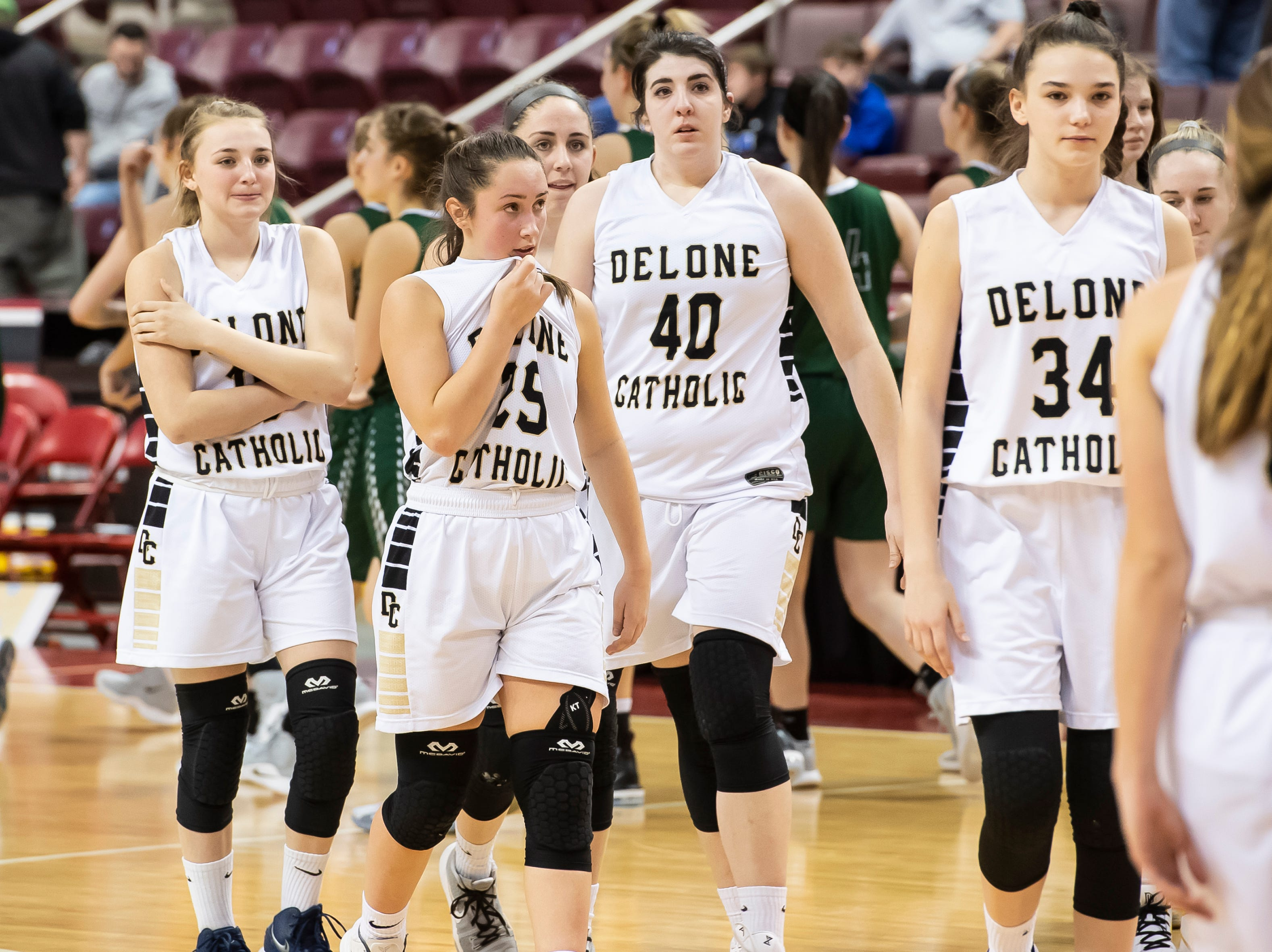 Delone Catholic players walk on the court after falling to Trinity in the District 3 3A girls championship game against Trinity at the Giant Center in Hershey Wednesday, Feb. 27, 2019. The Squirettes fell 44-33.