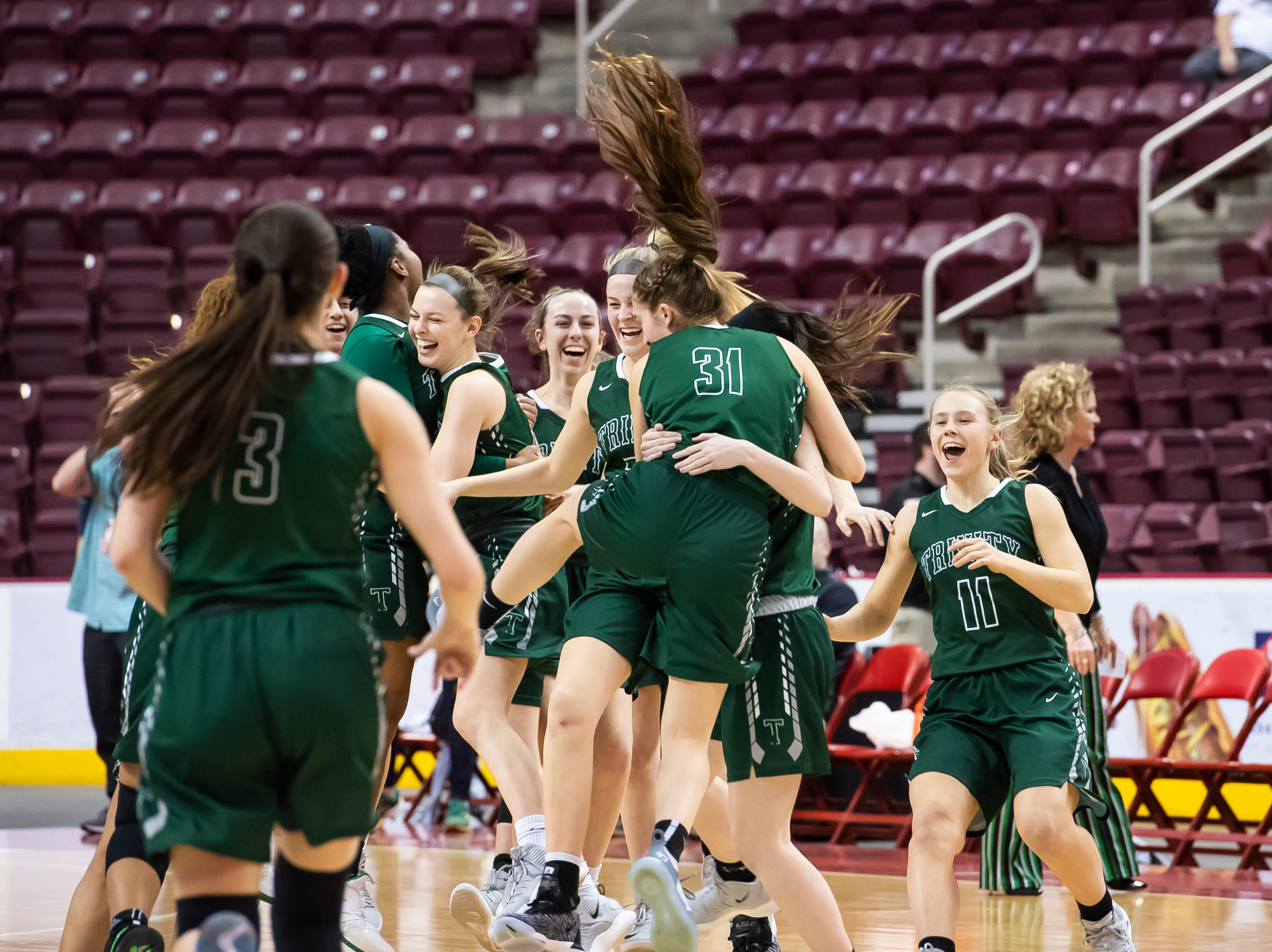 The Trinity Shamrocks celebrate after defeating Delone Catholic in the District 3 3A girls championship game against Trinity at the Giant Center in Hershey Wednesday, Feb. 27, 2019. The Squirettes fell 44-33.