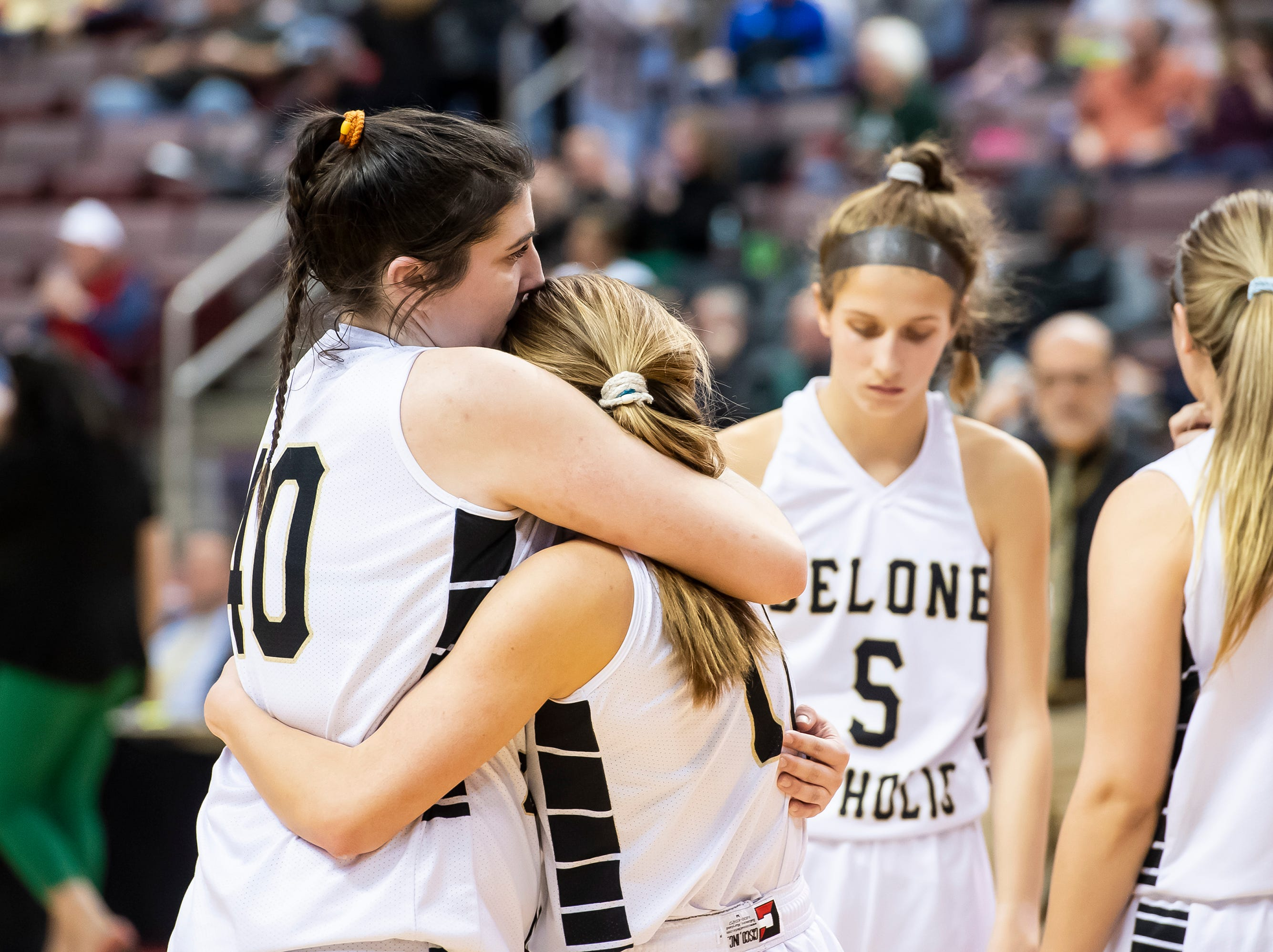 Delone Catholic's Bradi Zumbrum, left, and Riley Vingsen hug after falling to Trinity in the District 3 3A girls championship game against Trinity at the Giant Center in Hershey Wednesday, Feb. 27, 2019. The Squirettes fell 44-33.