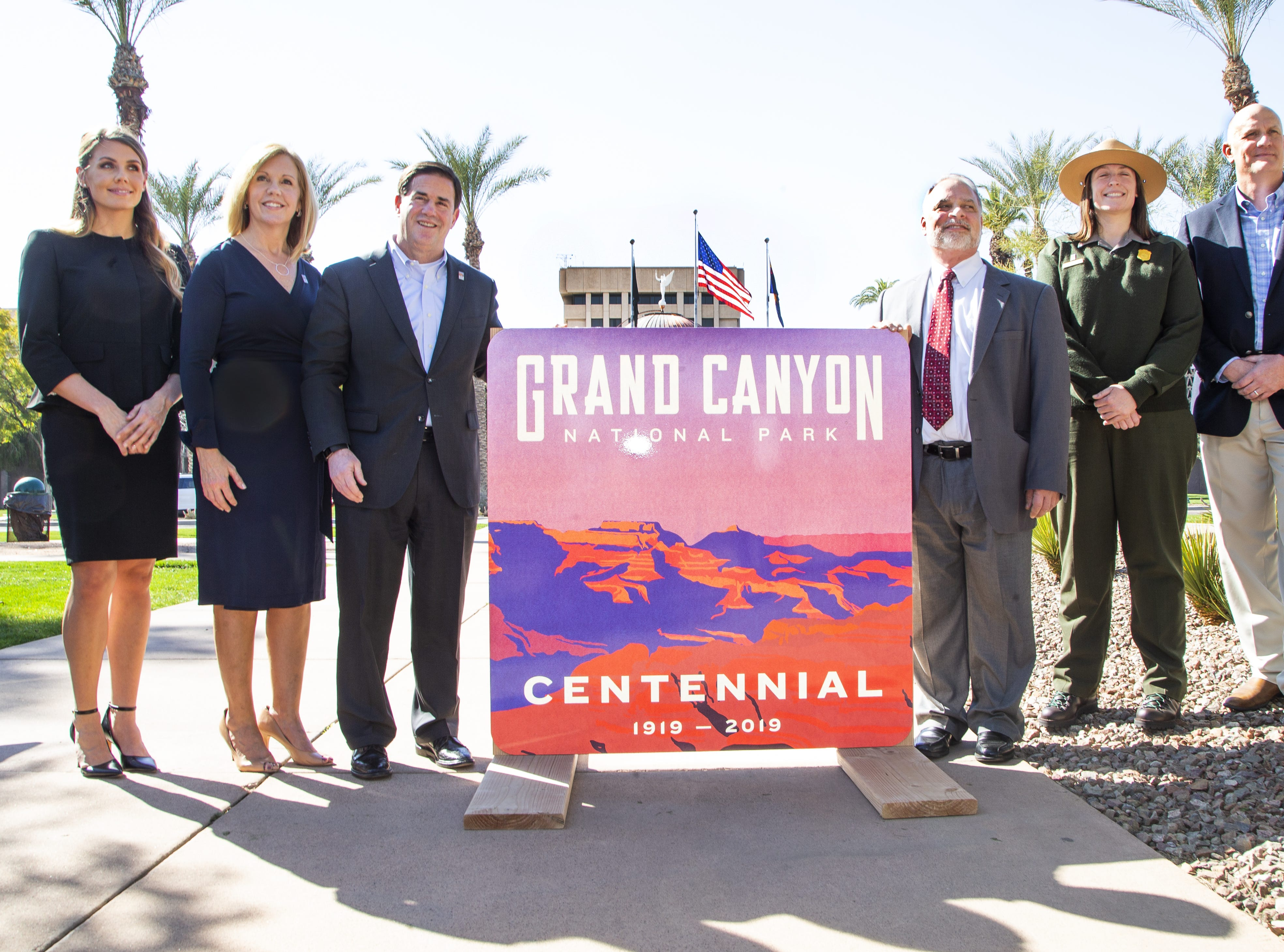 Gov. Doug Ducey helped to unveil a new sign marking the 100-year birthday of the Grand Canyon during a ceremony in Wesley Bolin Memorial Plaza at the Capitol in Phoenix, February 27, 2019. From left to right are, Katie Prendergast, Arizona Public Service; Debbie Johnson, director of the Arizona Office of Tourism; Gov. Ducey; John Halikowski, Arizona Department of Transportation director; Grand Canyon National Park Ranger Sara Bateman; Robert Broscheid, executive director of Arizona State Parks and Trails.