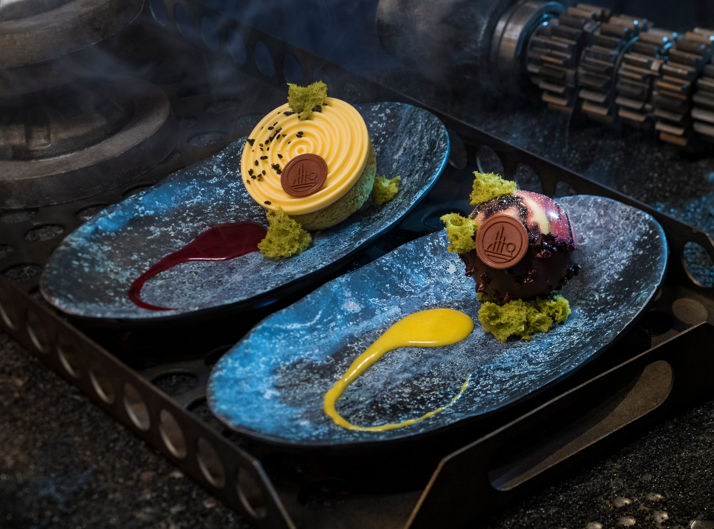 Guests can indulge in a raspberry creme puff with passion fruit mousse (left) or chocolate cake with white chocolate mouse and coffee custard (right) at Docking Bay 7 Food and Cargo inside Star Wars: Galaxy's Edge.