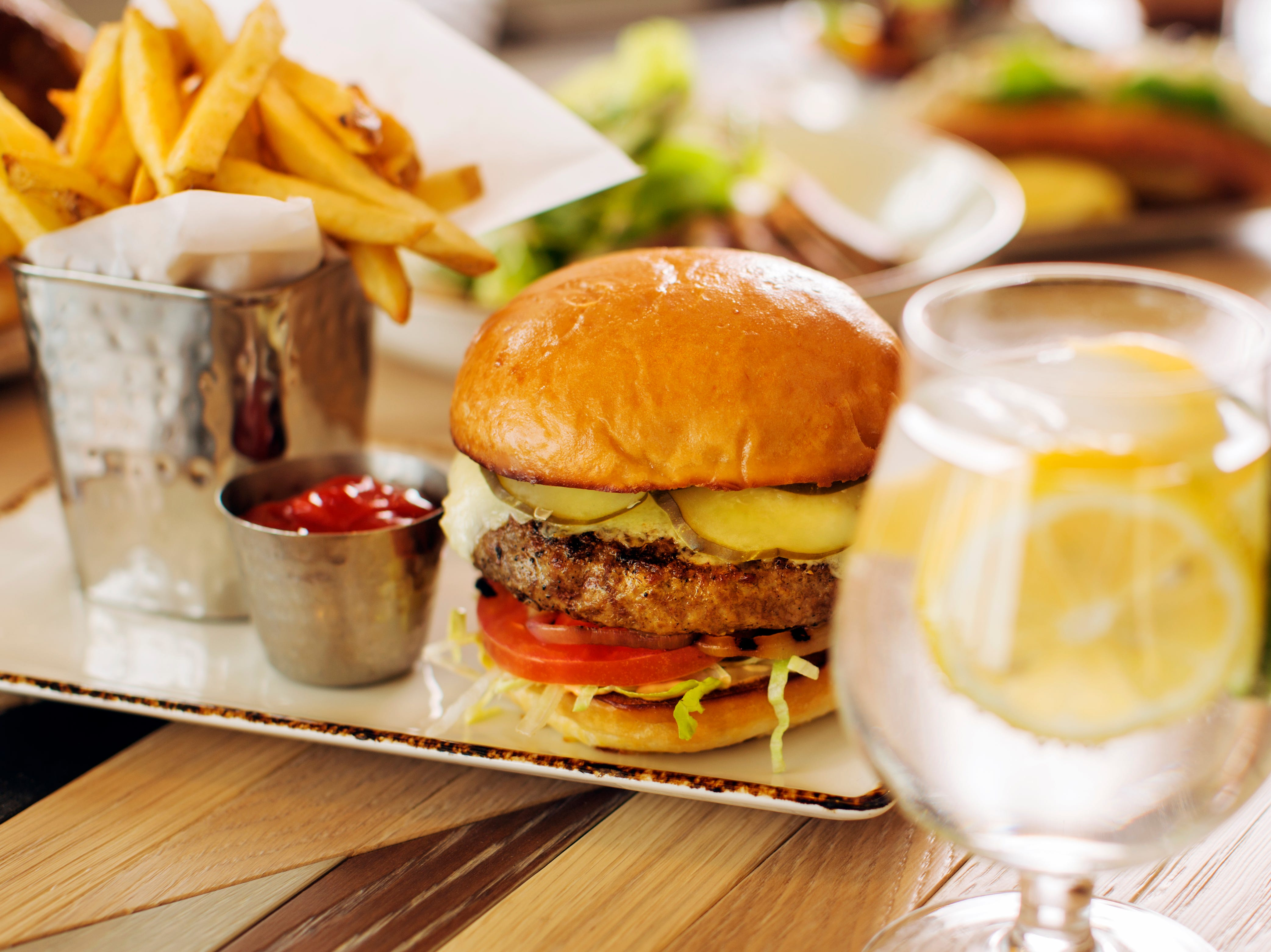 Main offerings at The Phoenician Tavern include six specialty burgers, among them the Lamb Burger topped with arugula, chimichurri, ricotta and lamb bacon, and The Cowboy featuring a free range bison patty with fried onions, jalapeños, bacon, sharp cheddar and steak sauce.