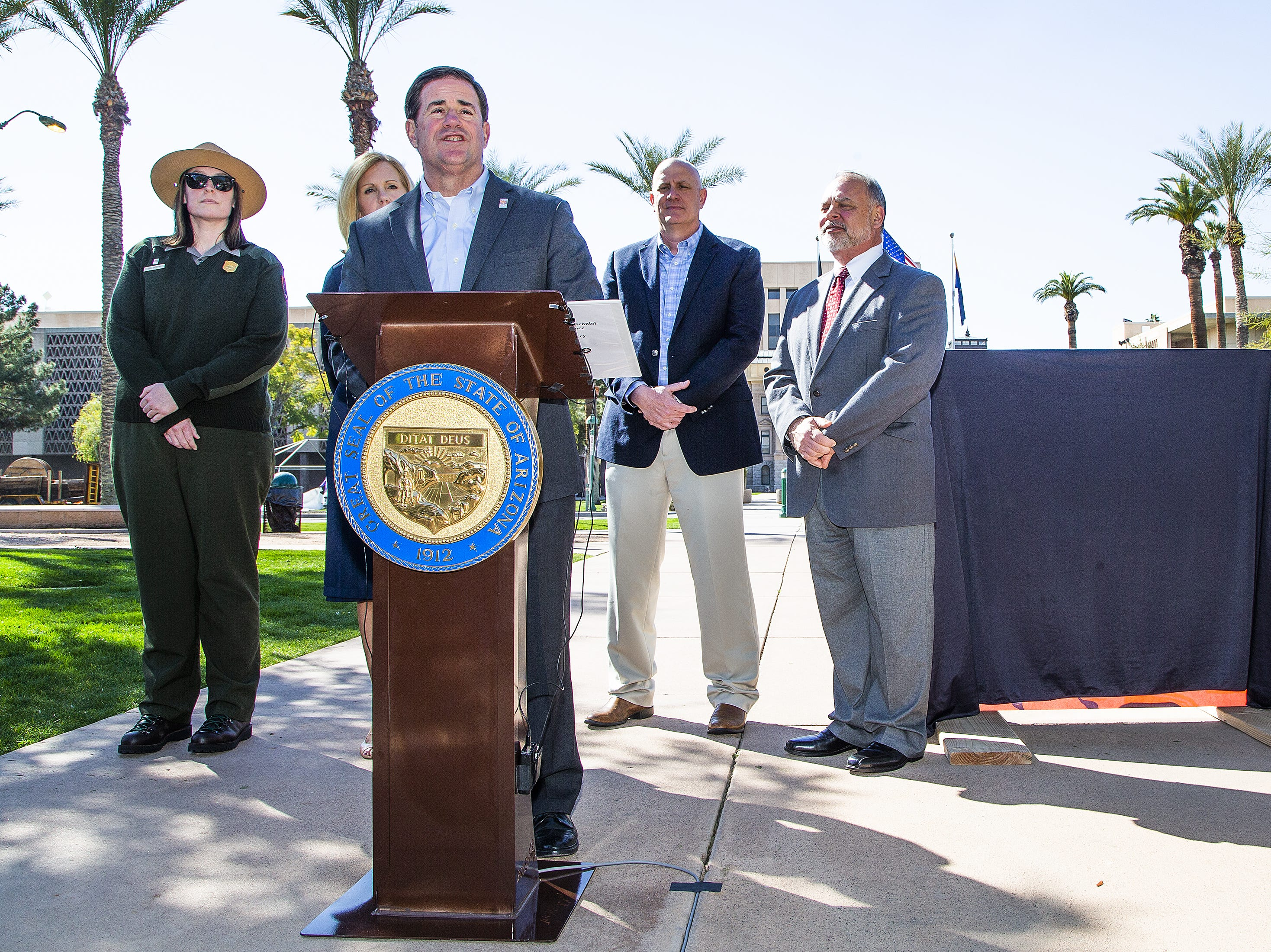 Gov. Doug Ducey, center, prepares to unveil a new sign marking the 100-year birthday of the Grand Canyon during a ceremony in Wesley Bolin Memorial Plaza at the Capitol in Phoenix, February 27, 2019. From left to right are, Grand Canyon National Park Ranger Sara Bateman; Debbie Johnson, director of the Arizona Office of Tourism; Ducey; Robert  Broscheid, executive director of Arizona State Parks and Trails; John Halikowski, Arizona Department of Transportation director.