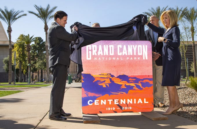 Gov. Doug Ducey, left, and Debbie Johnson, director of the Arizona Office of Tourism, right, unveil a new sign marking the 100-year birthday of the Grand Canyon during a ceremony in Wesley Bolin Memorial Plaza at the Capitol in Phoenix, February 27, 2019.