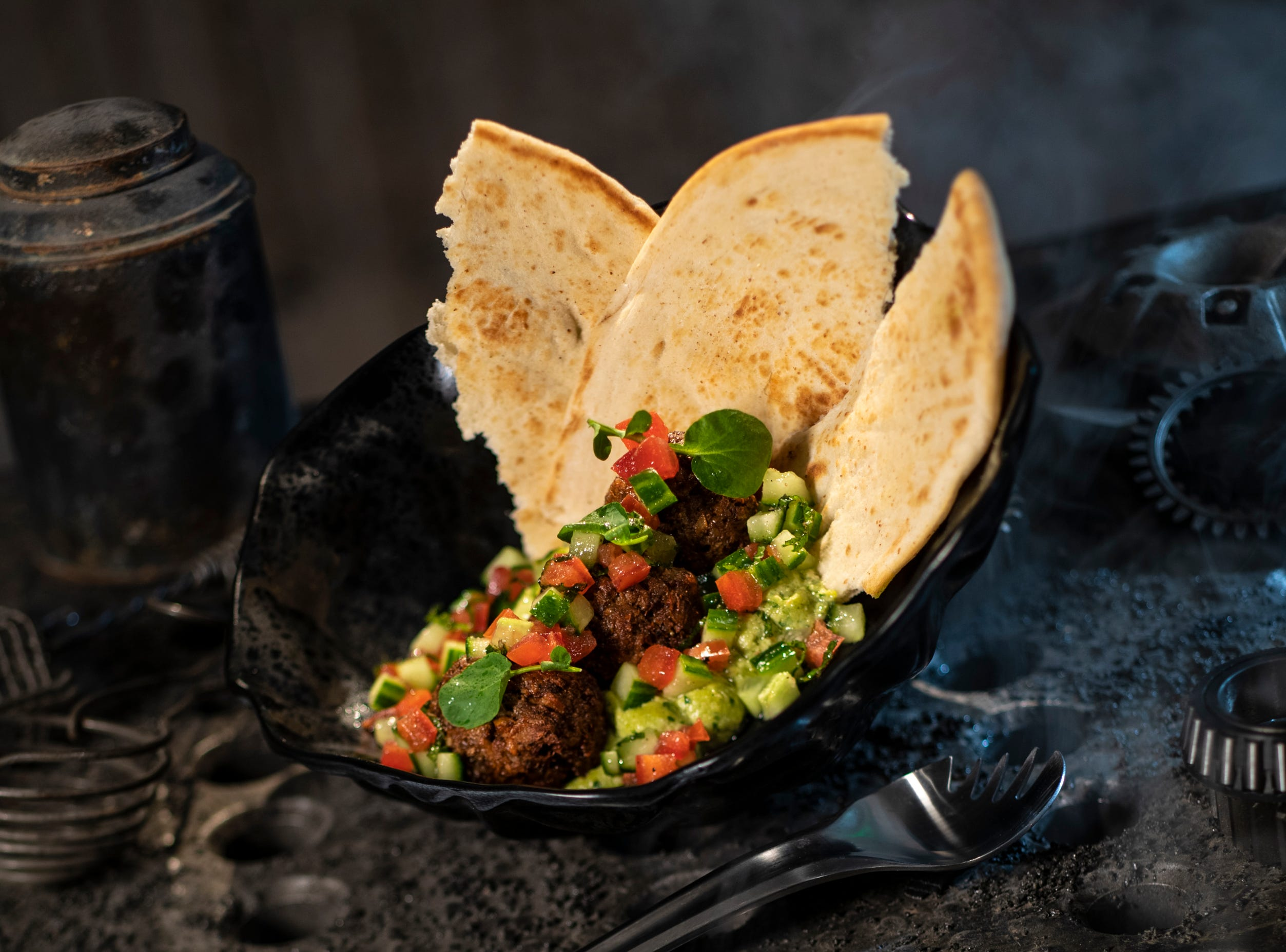 "The Felucian Garden Spread, found at Docking Bay 7 Food and Cargo inside Star Wars: Galaxy's Edge, is a plant-based kefta ""meatball"" dish with herb hummus and tomato-cucumber relish with pita bread."
