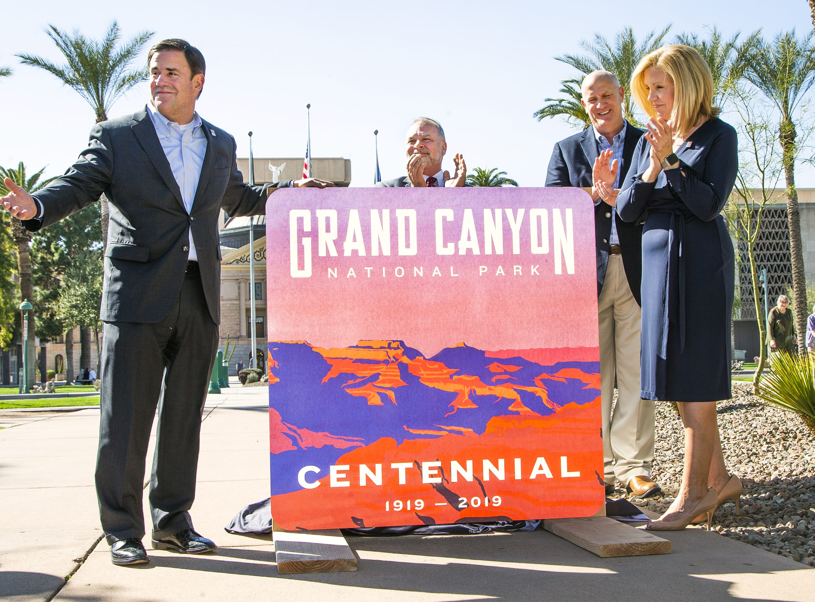 Gov. Doug Ducey, left, helps unveil a new sign marking the 100th birthday of the Grand Canyon during a ceremony in Wesley Bolin Memorial Plaza at the Capitol in Phoenix, February 27, 2019. From left to right are,  John Halikowski, Arizona Department of Transportation director; Robert  Broscheid, executive director of Arizona State Parks and Trails; Debbie Johnson, director of the Arizona Office of Tourism.