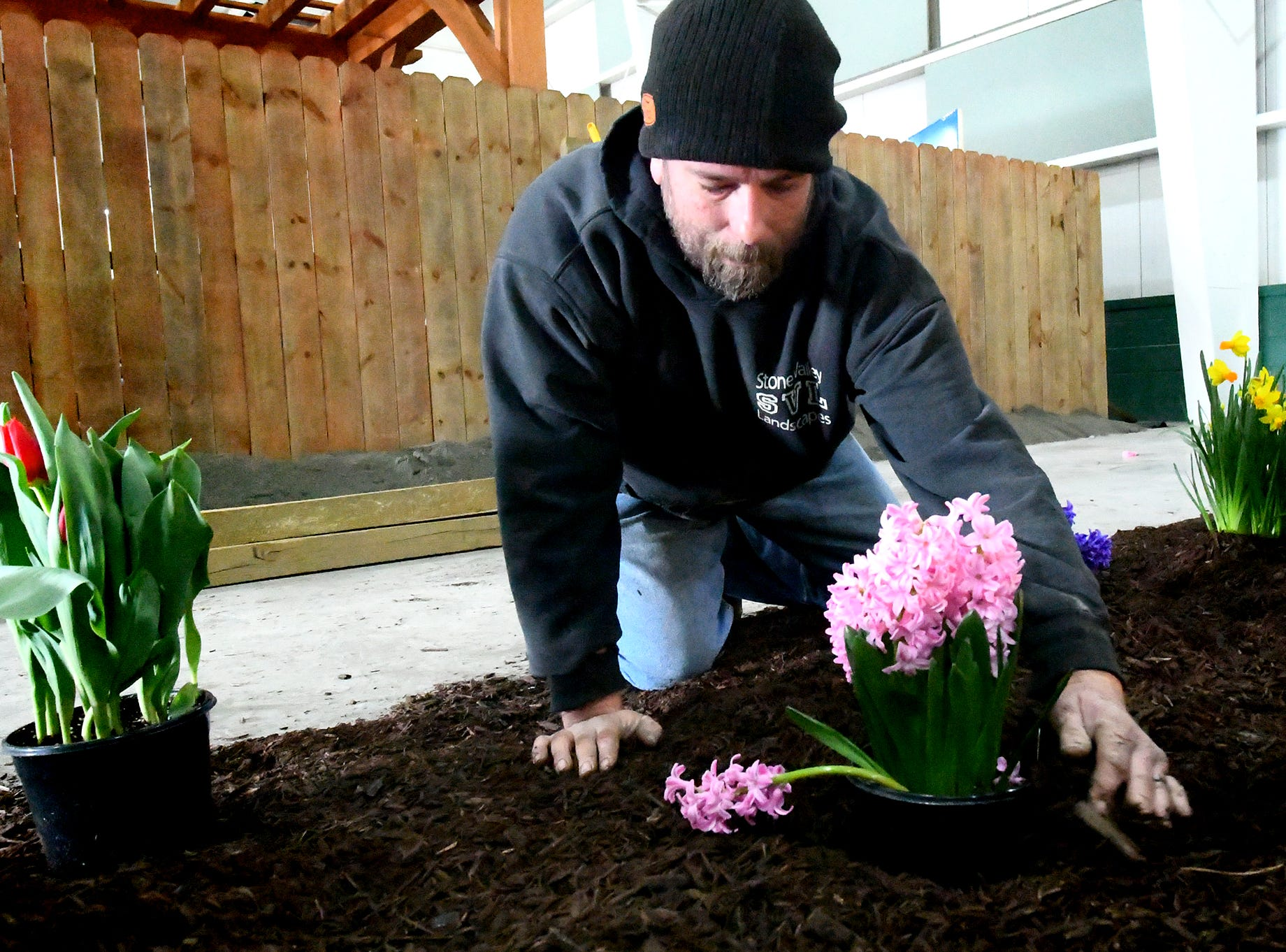 """James Trich of Stone Valley Landscapes places a hyacinth in a garden at the company's exhibit at the PA Garden Show of York Wednesday, Feb. 27, 2019. The show, themed """"Flowers on Parade,"""" is in Memorial Hall at the York Expo Center March 1-3. Hours Friday and Saturday are 10 a.m. to 8 p.m., and Sunday 10 a.m. to 5 p.m. Admission for adults is $10. Children are free with multi-day passes and and senior discounts offered. Bill Kalina photo"""