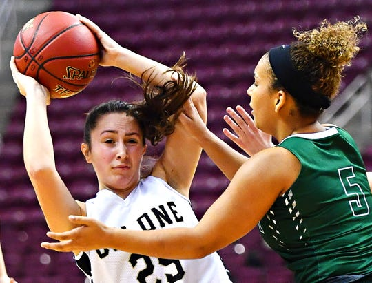 Delone Catholic's Camryn Felix, left, looks to get the ball past Trinity's Jaylin Moore during District 3, Class 3-A girls' basketball championship action at Giant Center in Hershey, Wednesday, Feb. 27, 2019. Trinity would win the title game 44-33. Dawn J. Sagert photo