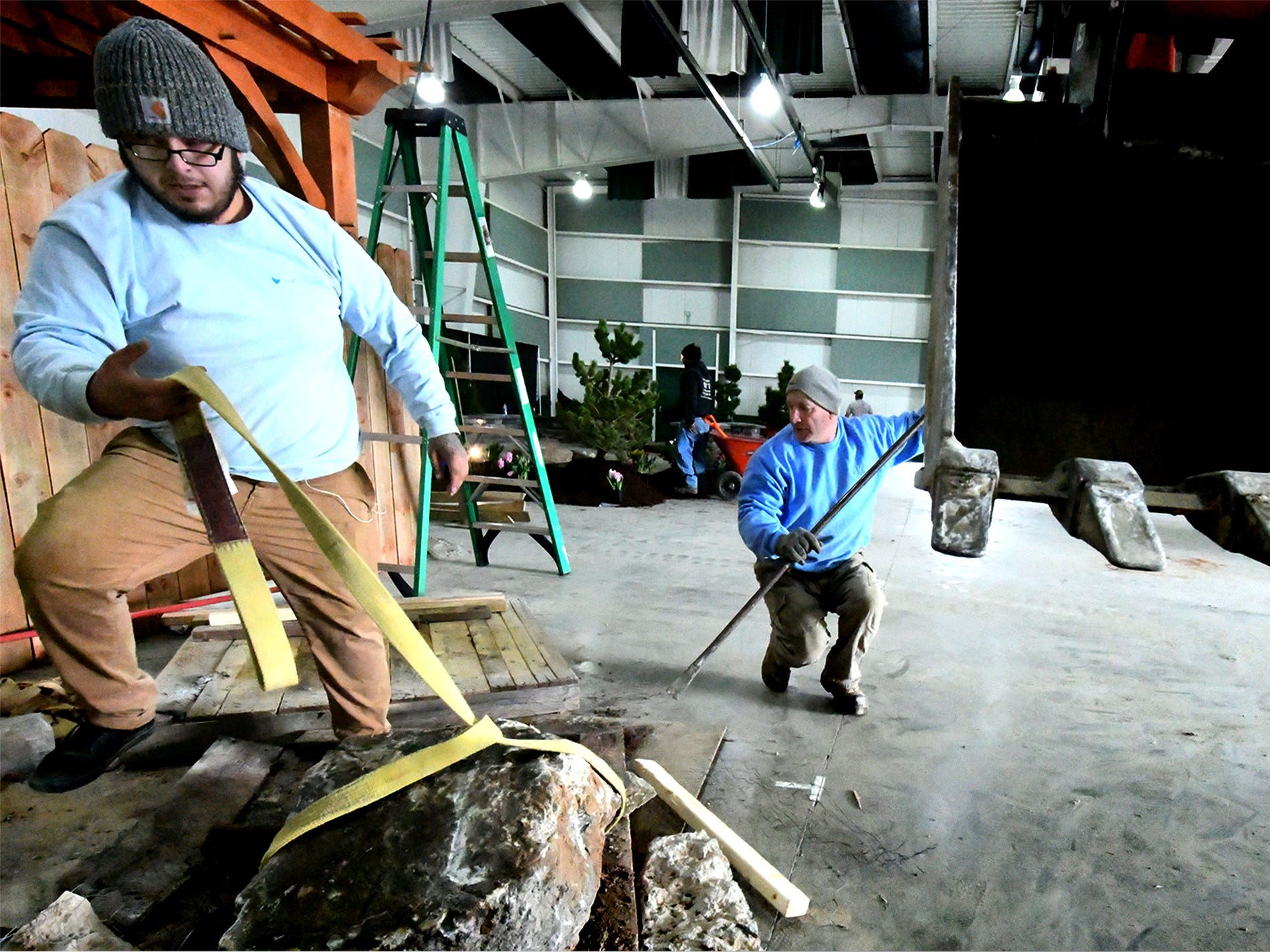 """Songbird Ponds employee Roy Martinez, left, and owner Roger Sears prepare to place landscape boulders at the company's exhibit at the PA Garden Show of York Wednesday, Feb. 27, 2019. The show, themed """"Flowers on Parade,"""" is in Memorial Hall at the York Expo Center March 1-3. Hours Friday and Saturday are 10 a.m. to 8 p.m., and Sunday 10 a.m. to 5 p.m. Admission for adults is $10. Children are free with multi-day passes and and senior discounts offered. Bill Kalina photo"""