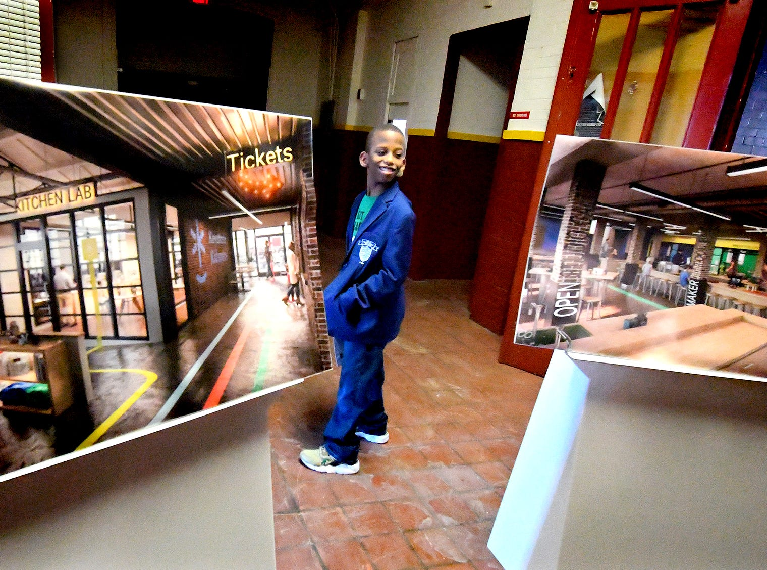 Lincoln Charter School ambassador Honor Franklin, a fourth-grader, stand between artist's renderings while touring the York Armory during a press event there Thursday, Feb. 28, 2019. Keystone Kidspace founders announced the launch of a $6 million capital campaign to transform the former armory building into an experiential learning center. Construction is slated to start this summer with an opening date of summer 2020. Bill Kalina photo